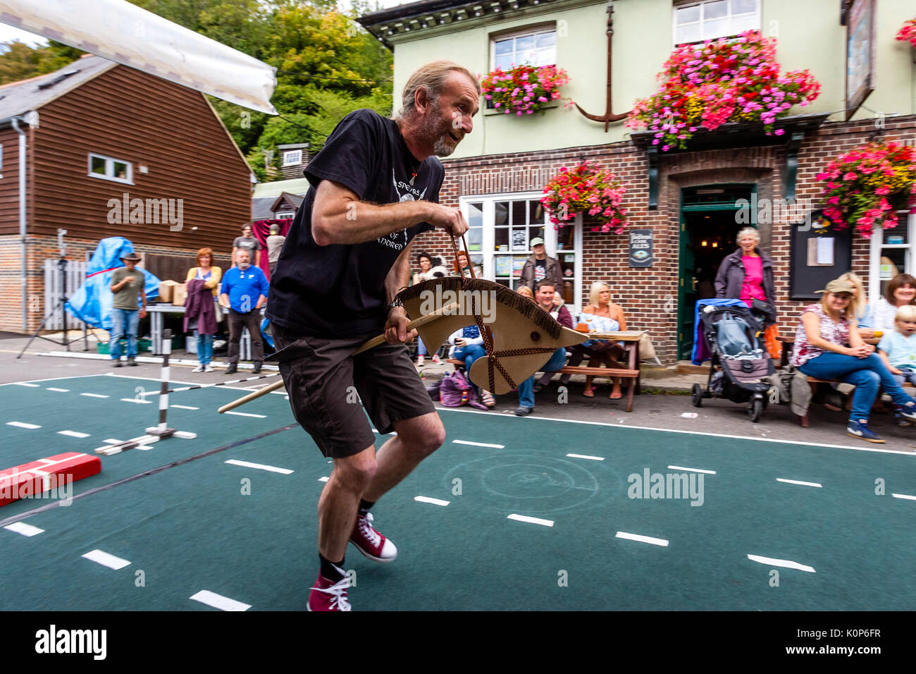 Local People 'Showjumping' With A Toy Horse At The Annual South Street Sports Day and Dog Show, Lewes, East Sussex, UK - Stock Image