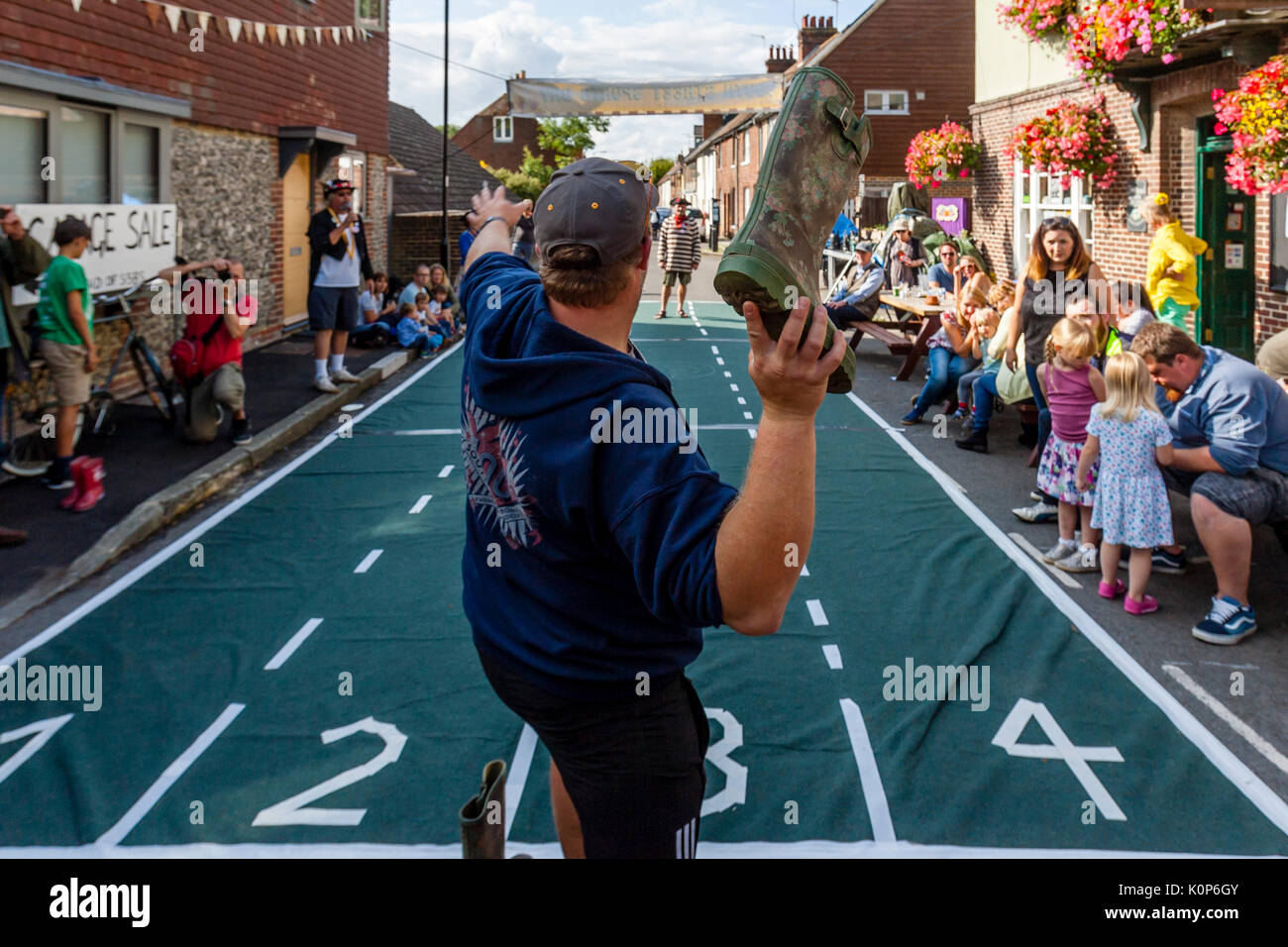 Local People Take Part In A 'Welly Throwing' Competition At The Annual South Street Sports Day and Dog Show, Lewes, East Sussex, UK - Stock Image