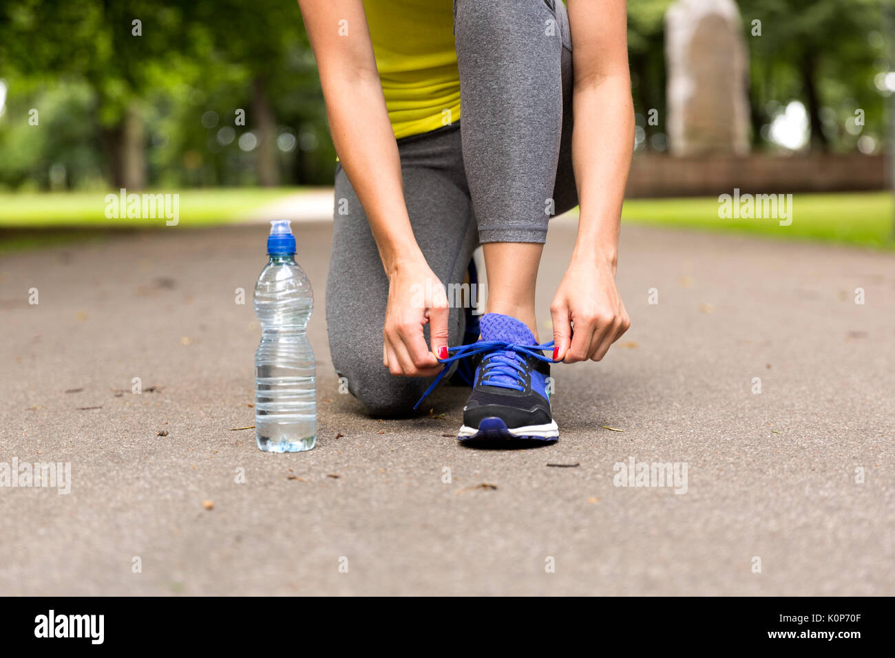 Young woman tying laces of running shoes before training. Healthy lifestyle concept - Stock Image