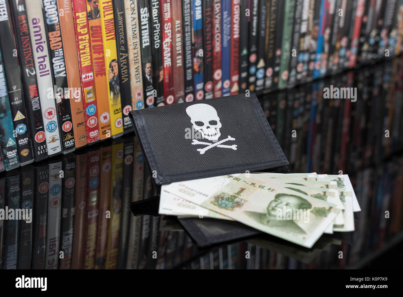 Stacked DVD movies & black pirate wallet with Chinese renminbi banknotes - metaphor for Chinese copyright and IP theft - US-China trade war. - Stock Image