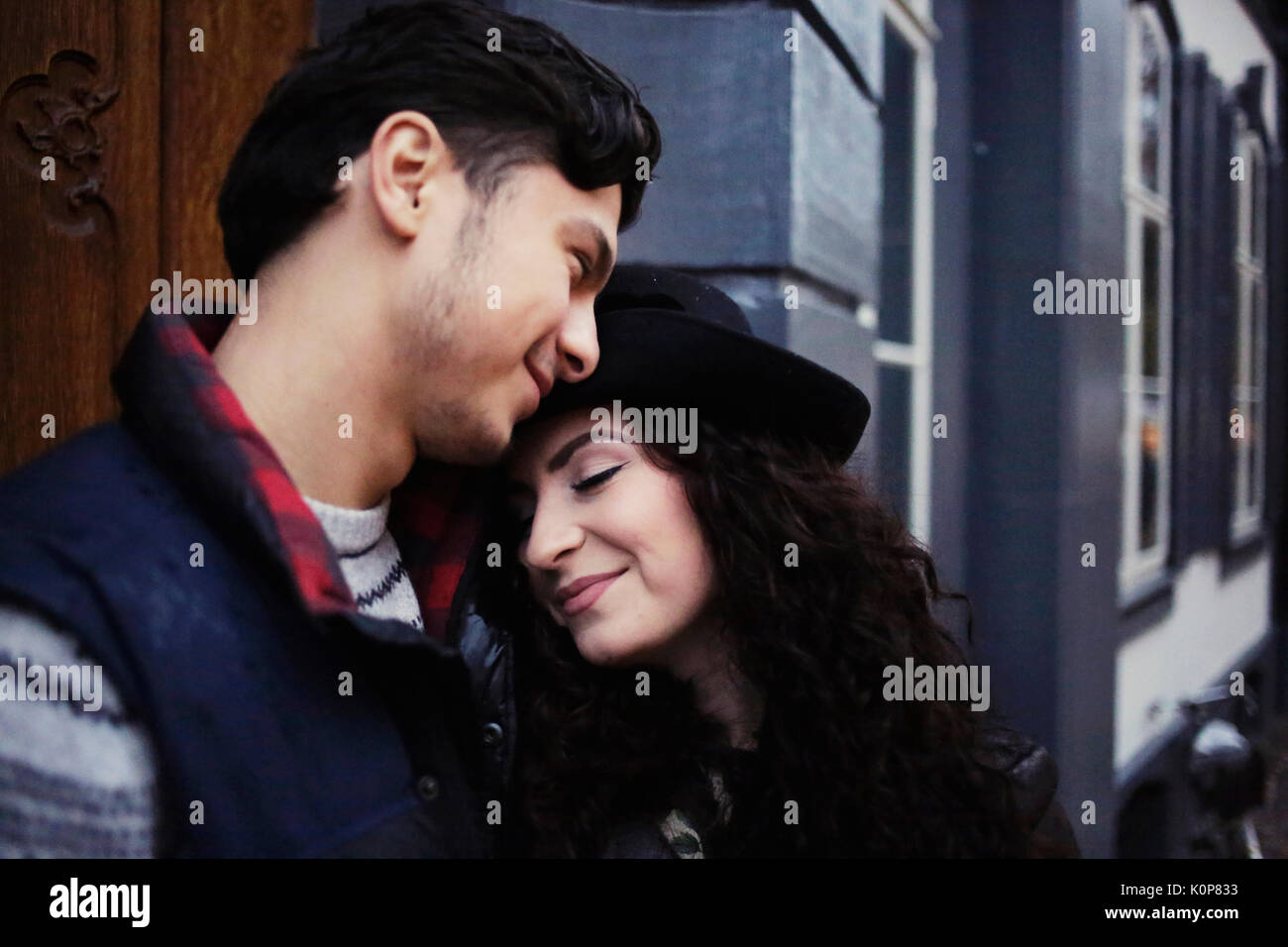 Young couple in front of house wall in love - Stock Image