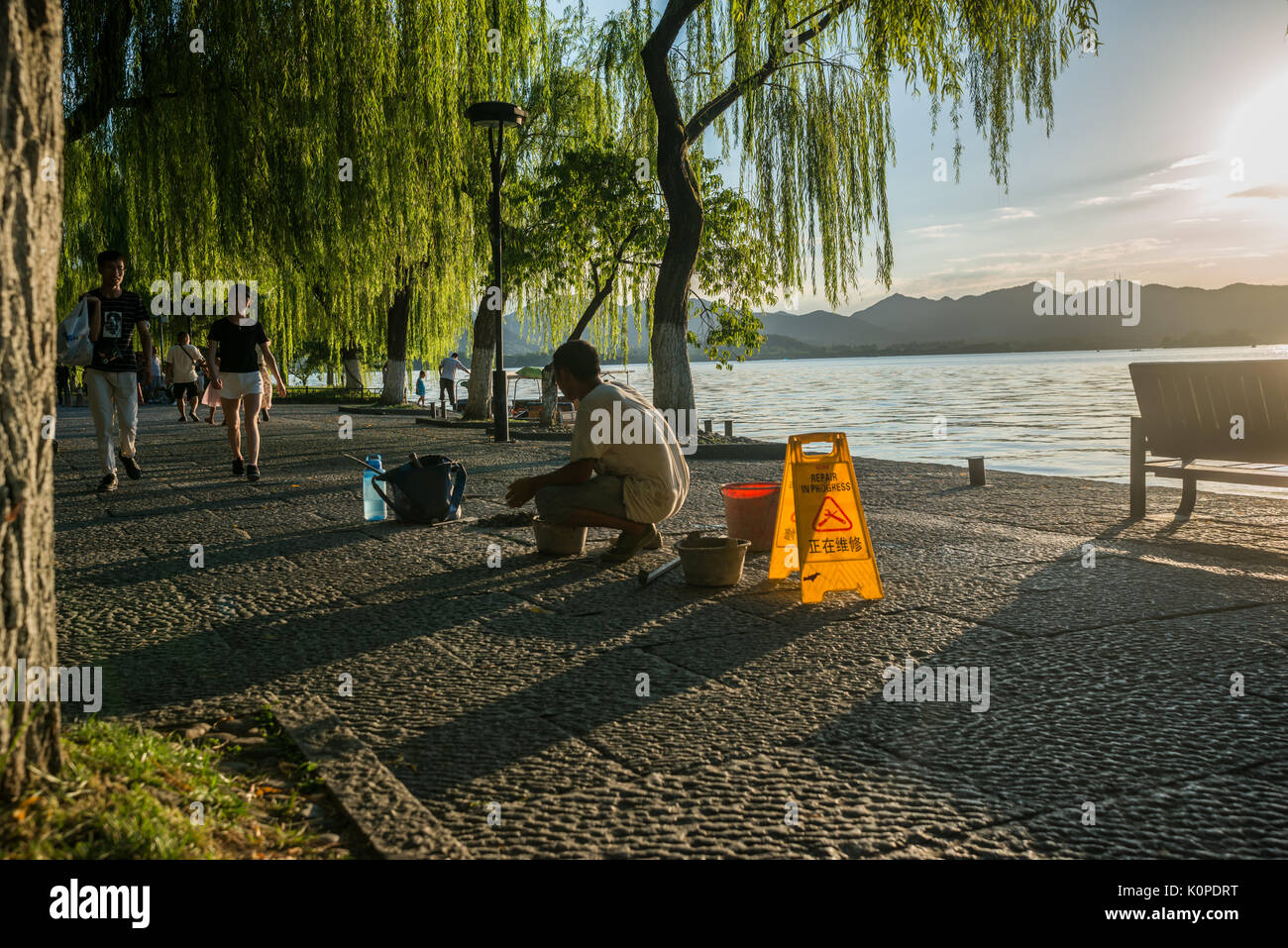 Chinese manual worker repairing the stone path, sidewalk in early evening - Stock Image