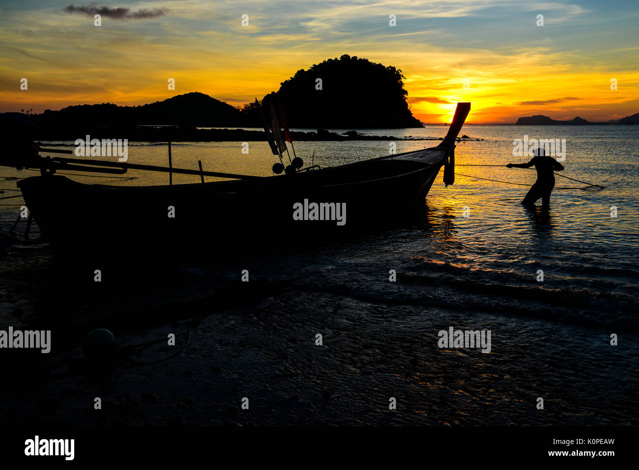 Fisherman pulling fishing boat to go into the sea in early morning. Stock Photo