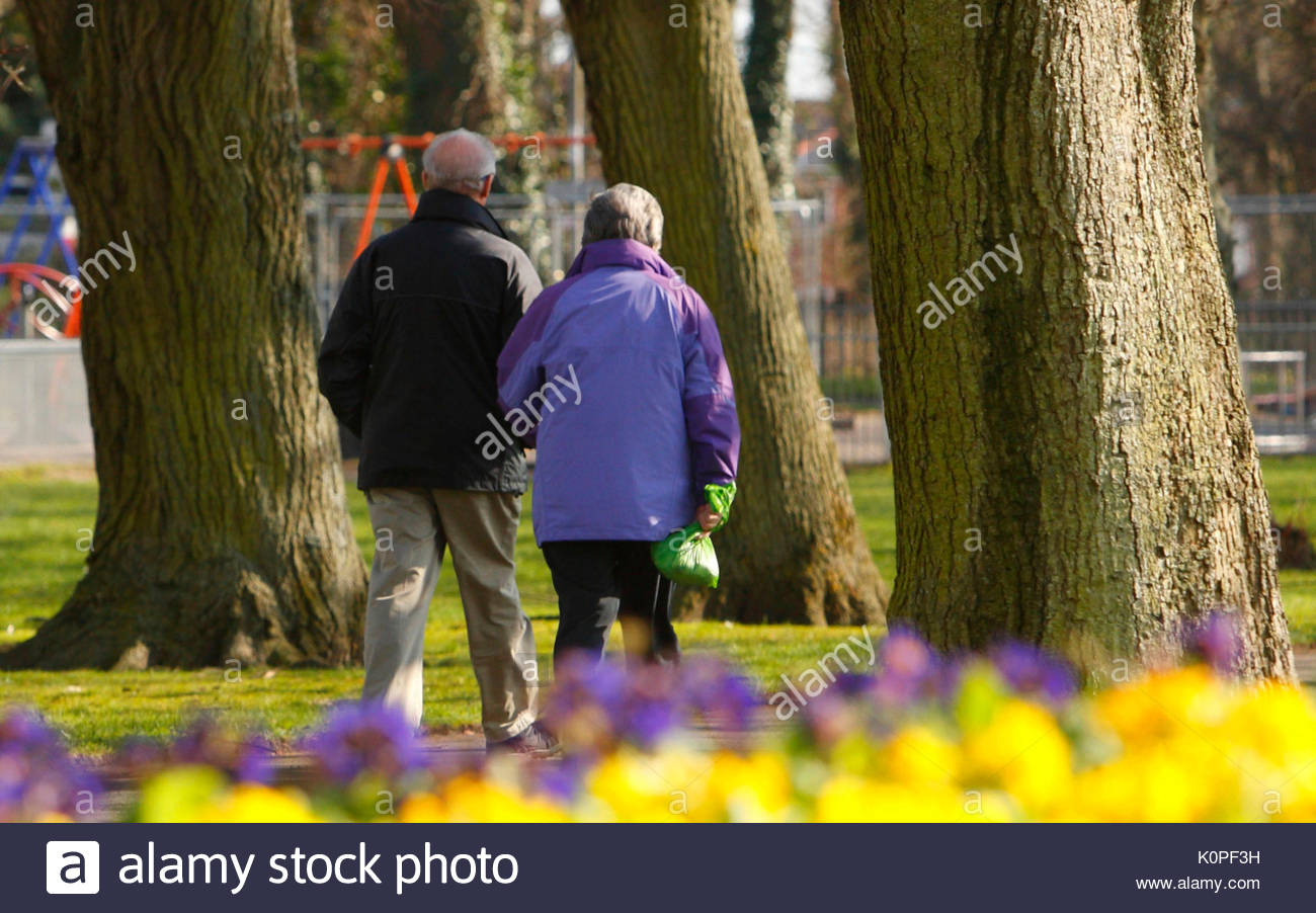 File photo dated 14/03/13 of a couple walking through a park. Shocking levels of inactivity among middle-aged people have been exposed in new research which revealed that more than six million English adults do not even manage a brisk 10-minute walk each month. - Stock Image