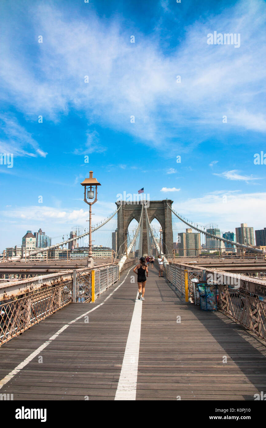 NEW YORK CITY, US – JUL, 2010: Woman jogging across the Brooklyn Bridge, NYC on a hot summer day with clear sky - Stock Photo