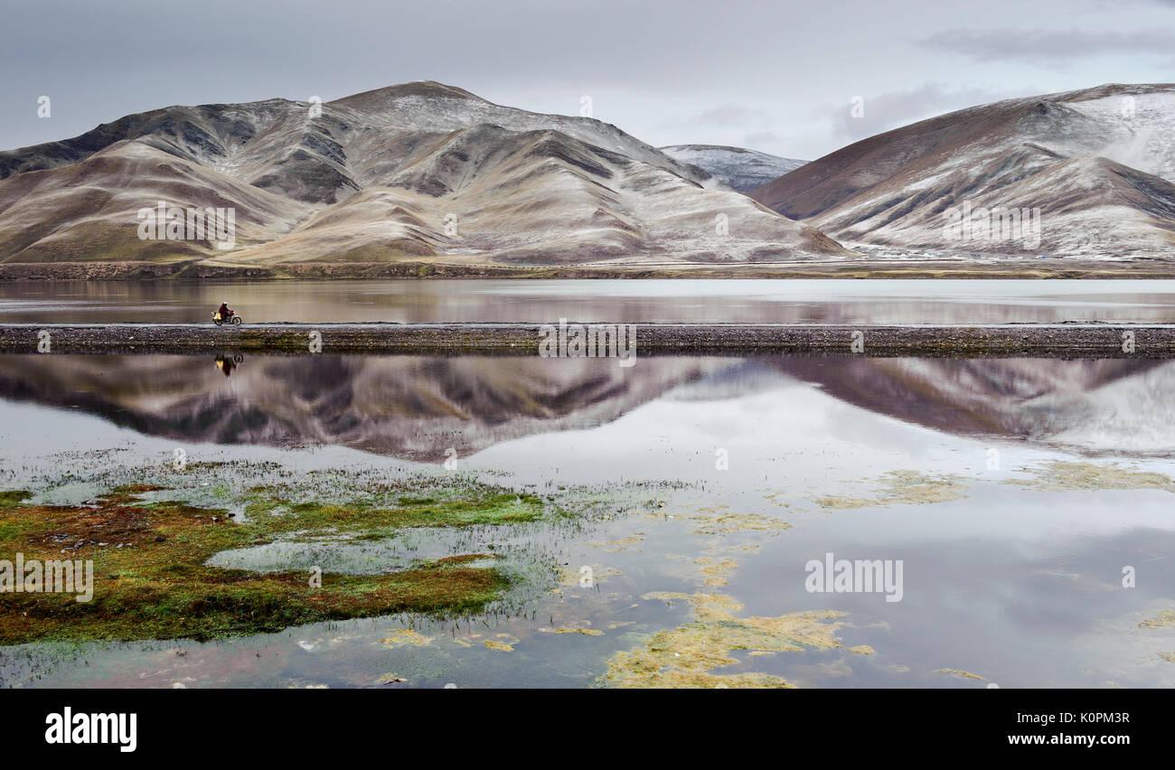 Tibetan monk on a motorcycle passing through a reservoir after a snowstorm near Sershul, Kham, Tibet - Stock Image