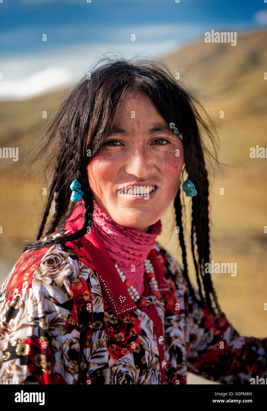 A Tibetan young woman wearing the traditional accessories typical of her ethnic group as well as her canines covered in gold, Remote Tibetan plateau - Stock Image