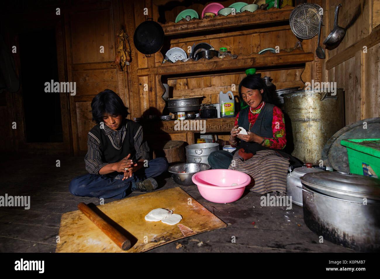 Tibetan mother and son cooking momos, the typical Tibetan dumpling, at home, Kham, Tibet - Stock Image