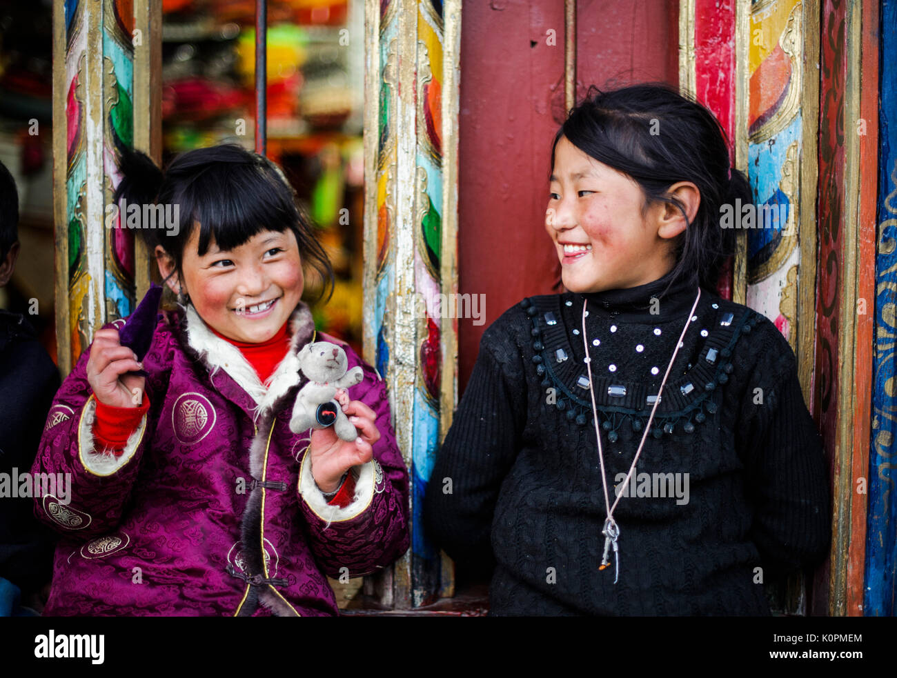 Two Tibetan kids playing at the front of a typical Tibetan decorated shop, in Kham province, Tibet - Stock Image