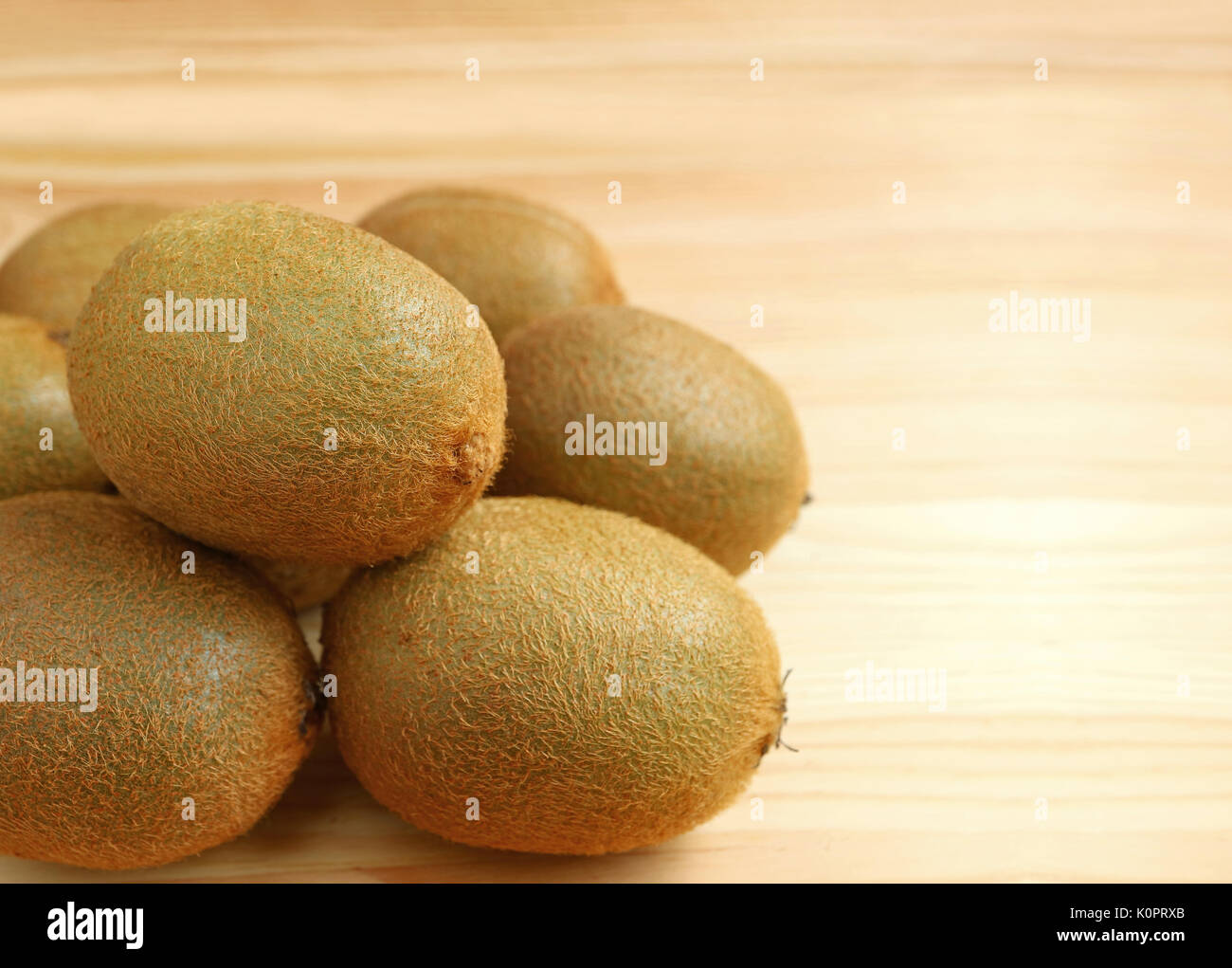 Pile of Fresh Ripe Kiwi Fruits on Wooden Table, with Selective Focus and Free Space for Design and Text - Stock Image