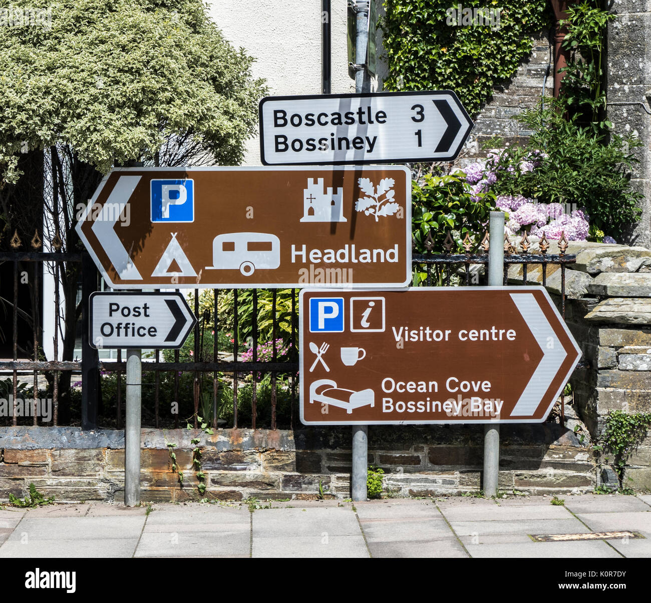 Multiple signs to various local places and tourist facilities, in the small town of Tintagel, Cornwall, England, UK. - Stock Image