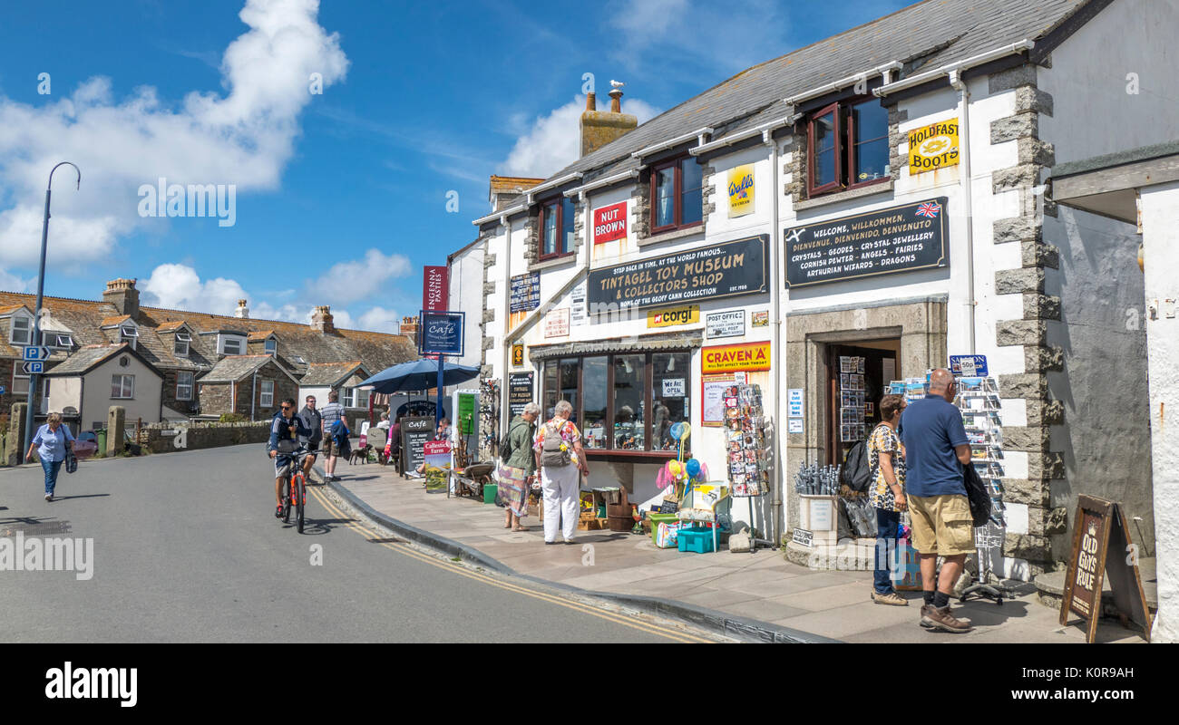 General view of people looking in shops along the start of Fore Street in the small tourist town of Tintagel on a summer's day. Cornwall, England, UK. - Stock Image