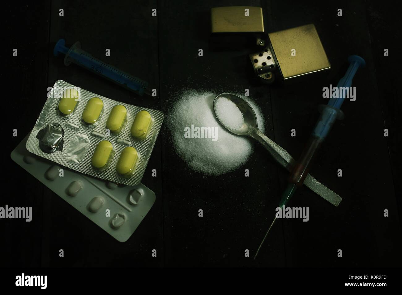 Hard drugs on dark table. A dark theme, drug use. Preparation of drugs, still life. Syringe with needle, spoon, tablets, lighter. Death. - Stock Image