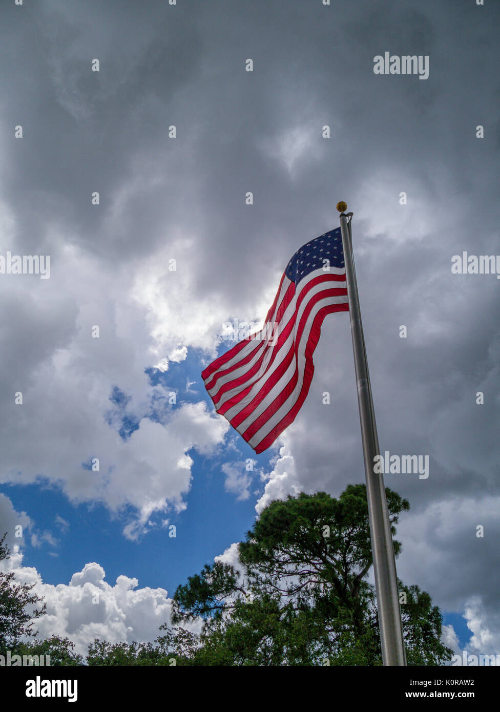 American flag flying aganist a dark cloudy sky - Stock Image