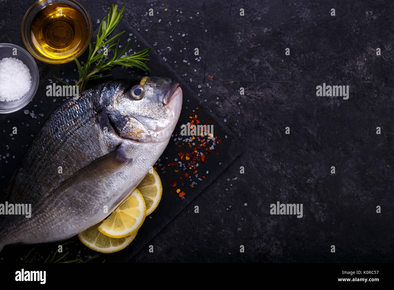 Fresh raw sea bream fish with lemon slices, salt, rosemary and olive oil on black slate background. Healthy food concept, top view, copy space - Stock Image