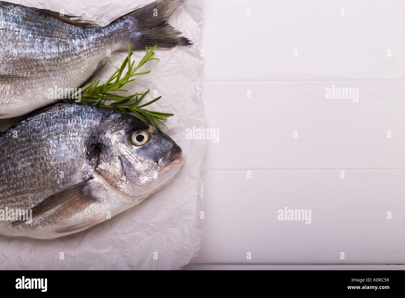 Fresh raw sea bream fish with lemon slices, salt, rosemary and olive oil on white wooden table.Healthy food concept, top view, copy space - Stock Image