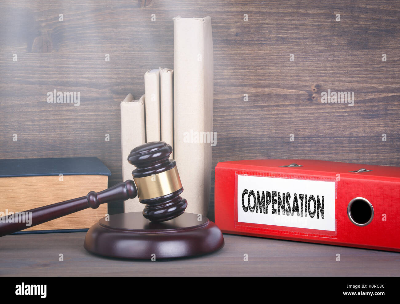 Compensation. Wooden gavel and books in background. Law and justice concept - Stock Image