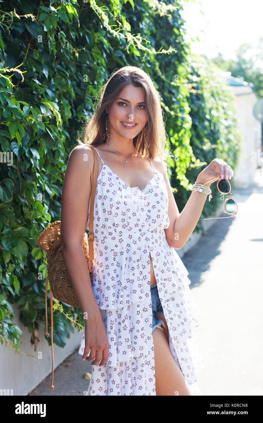 A hot summer in the city. Portrait of a girl in a light white dress posing on a hot day at the European street - Stock Image
