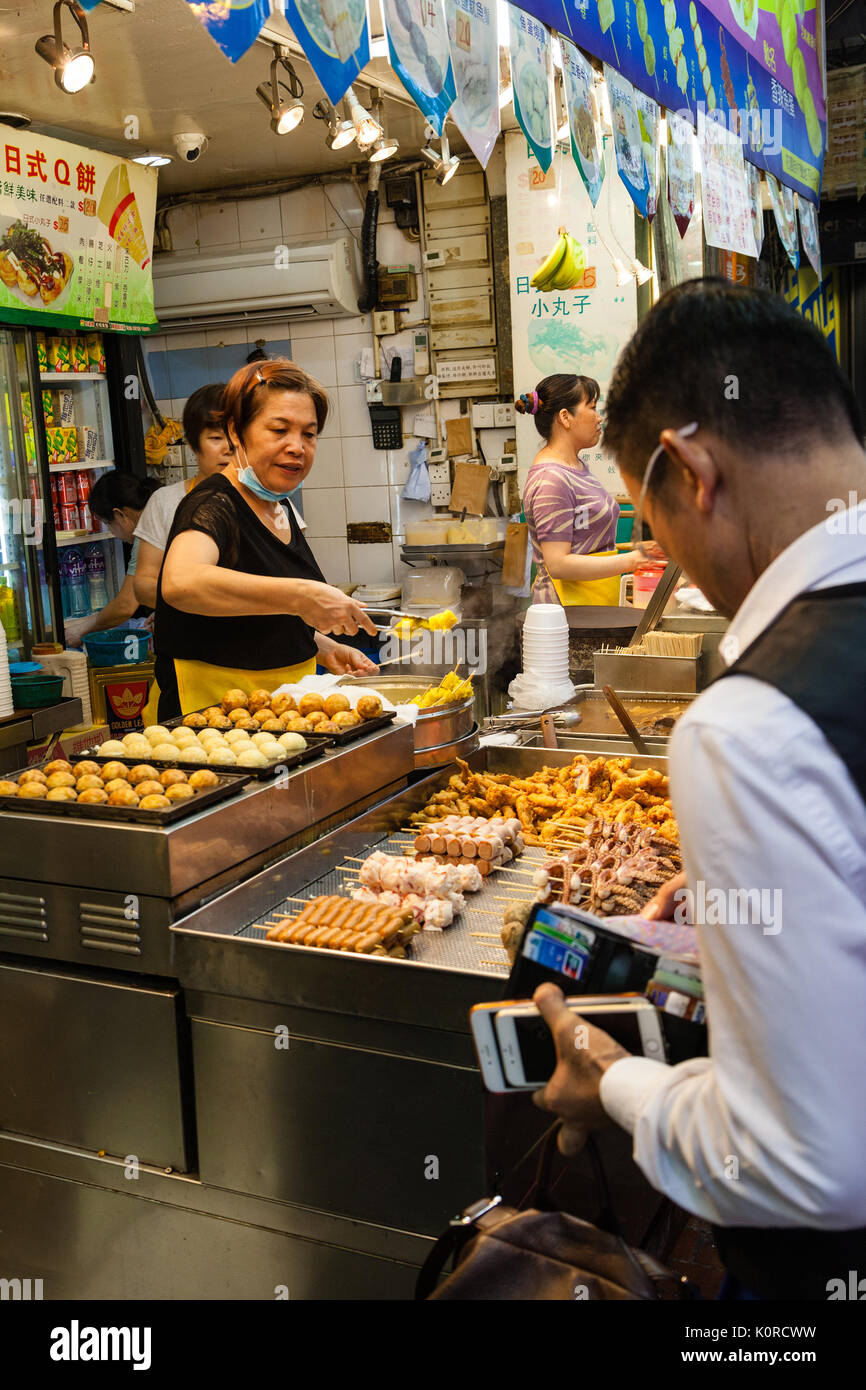 HONG KONG - JULY 11, 2017: A street vendor selling popular snacks at Fa Yuen Street night market in Kowloon. These include stinky tofu, pig intestines - Stock Image