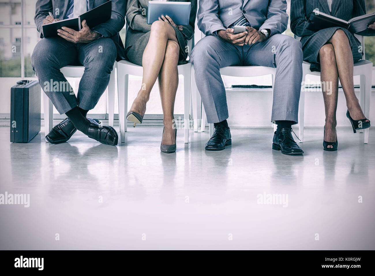Business people waiting to be called into interview at the office - Stock Image