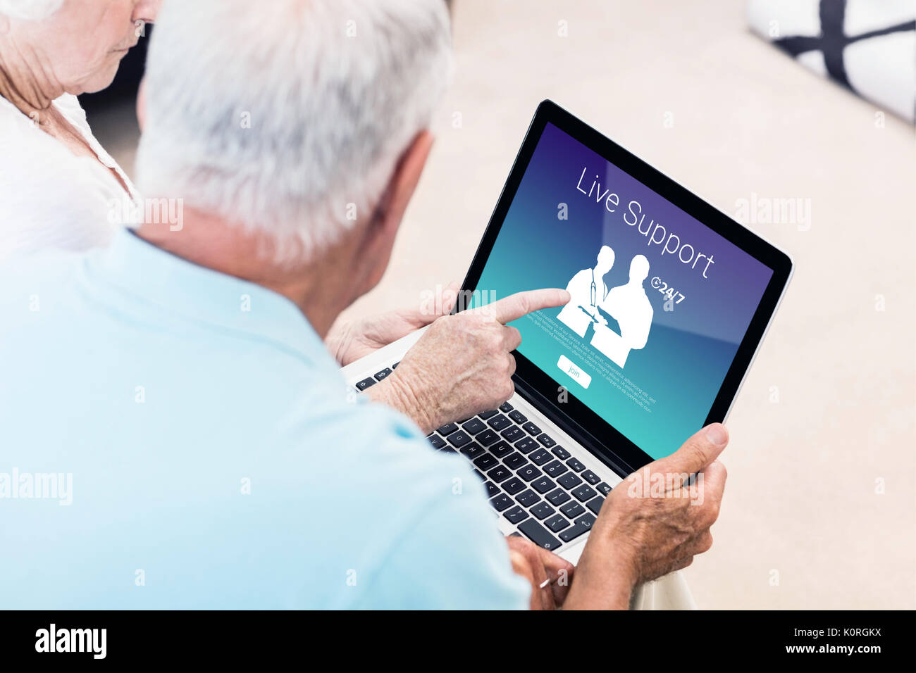 Human representations with live support text against focused senior couple using laptop Stock Photo
