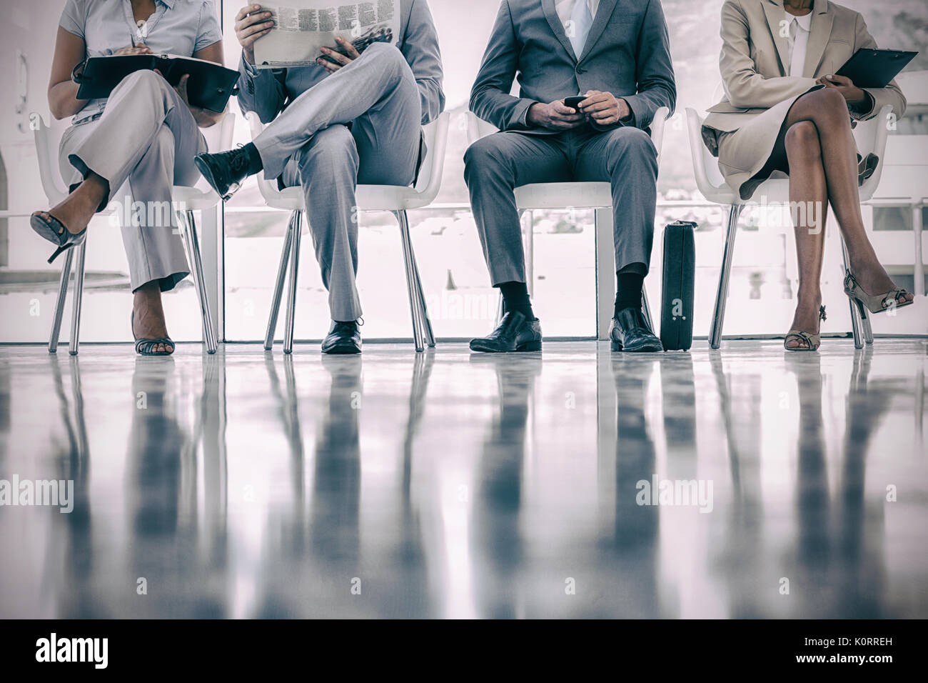 Group of well dressed business people waiting in waiting room - Stock Image