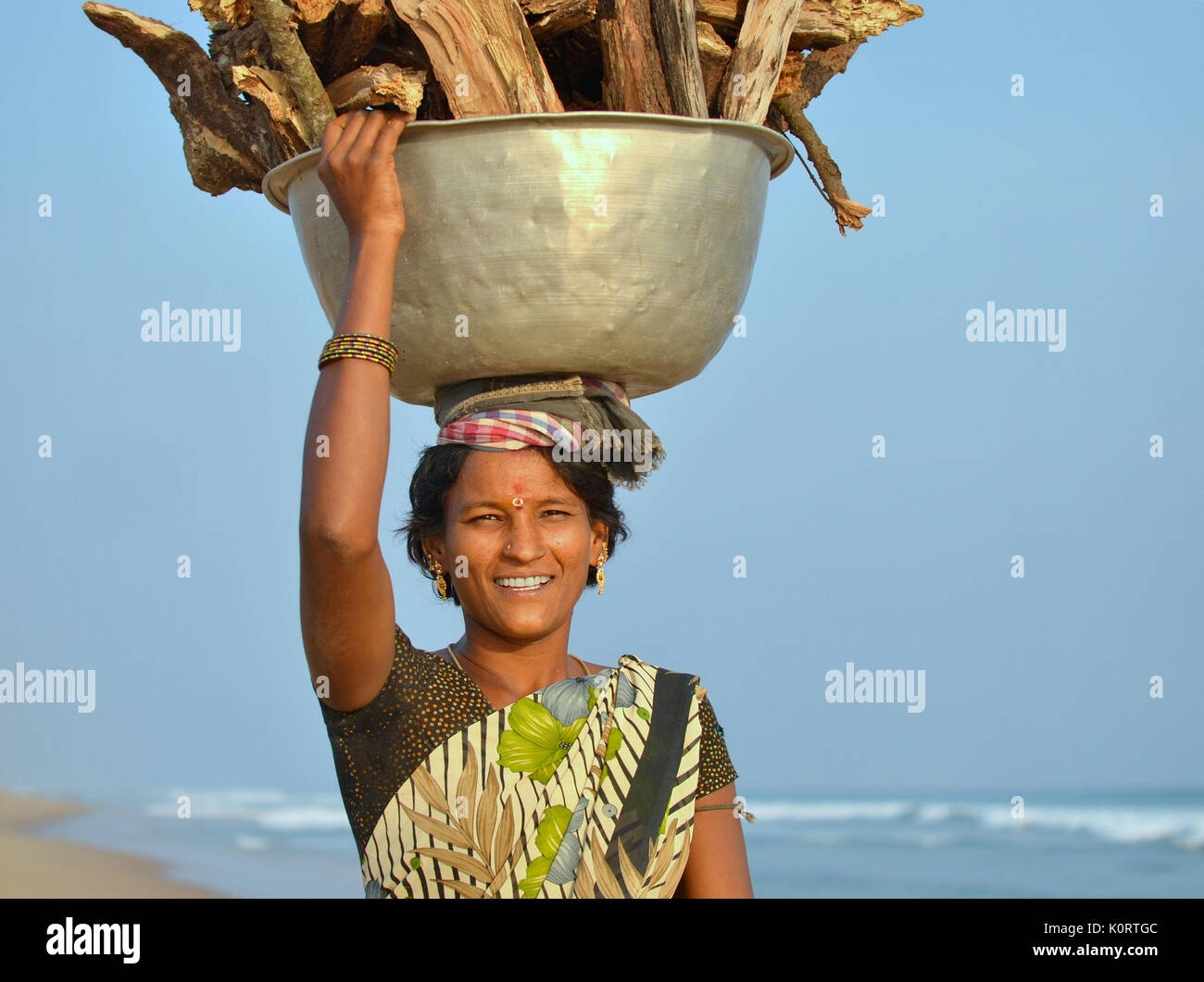 Young Orissan woman from the local fishing community at Puri, carrying a heavy load of firewood on her head. - Stock Image