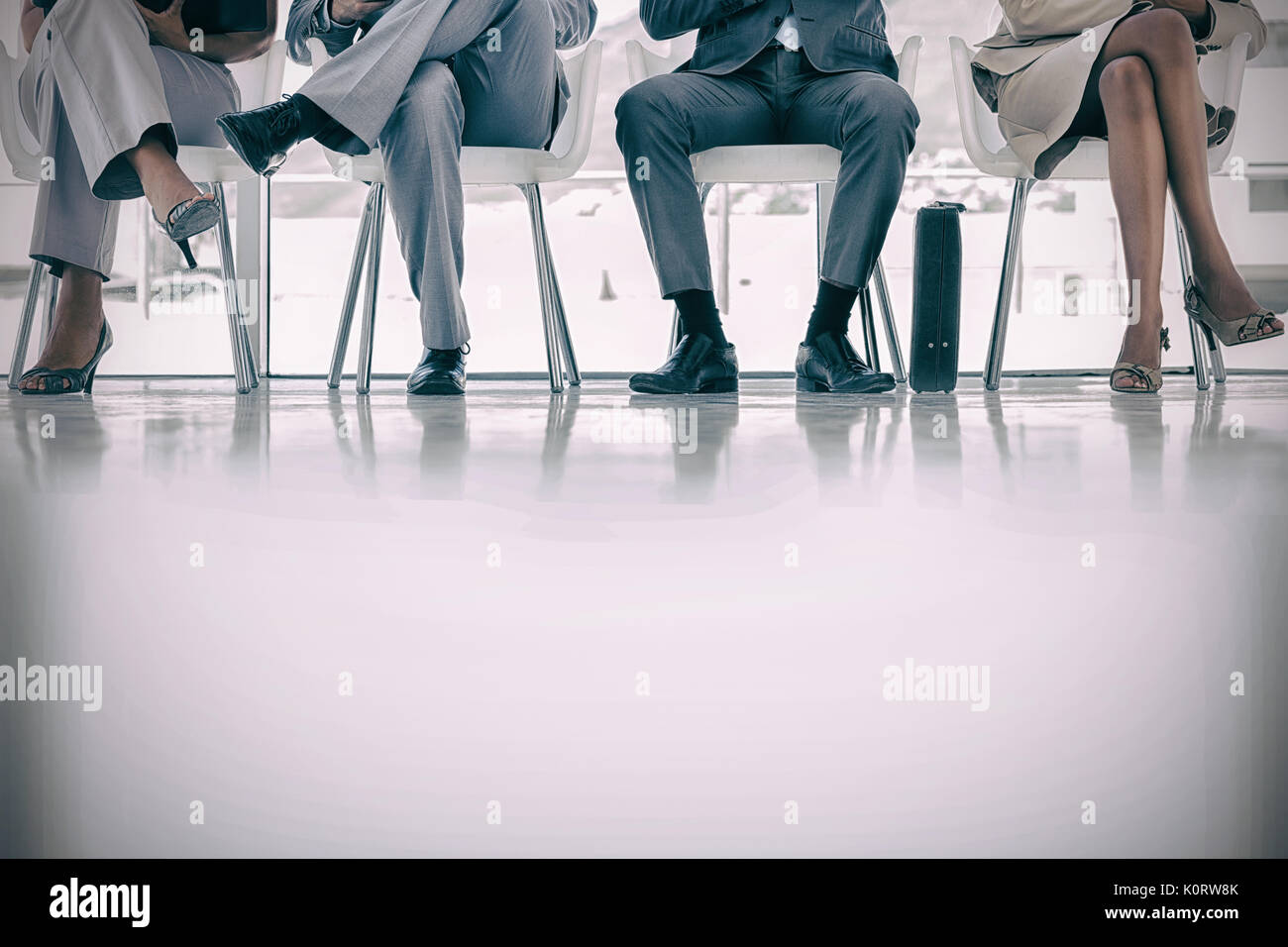 Waiting room with business people sitting in line at corridor - Stock Image
