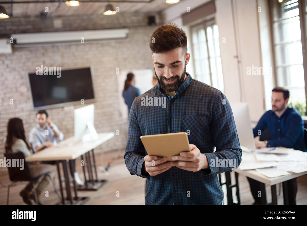 Portrait of young handsome male designer using tablet - Stock Image