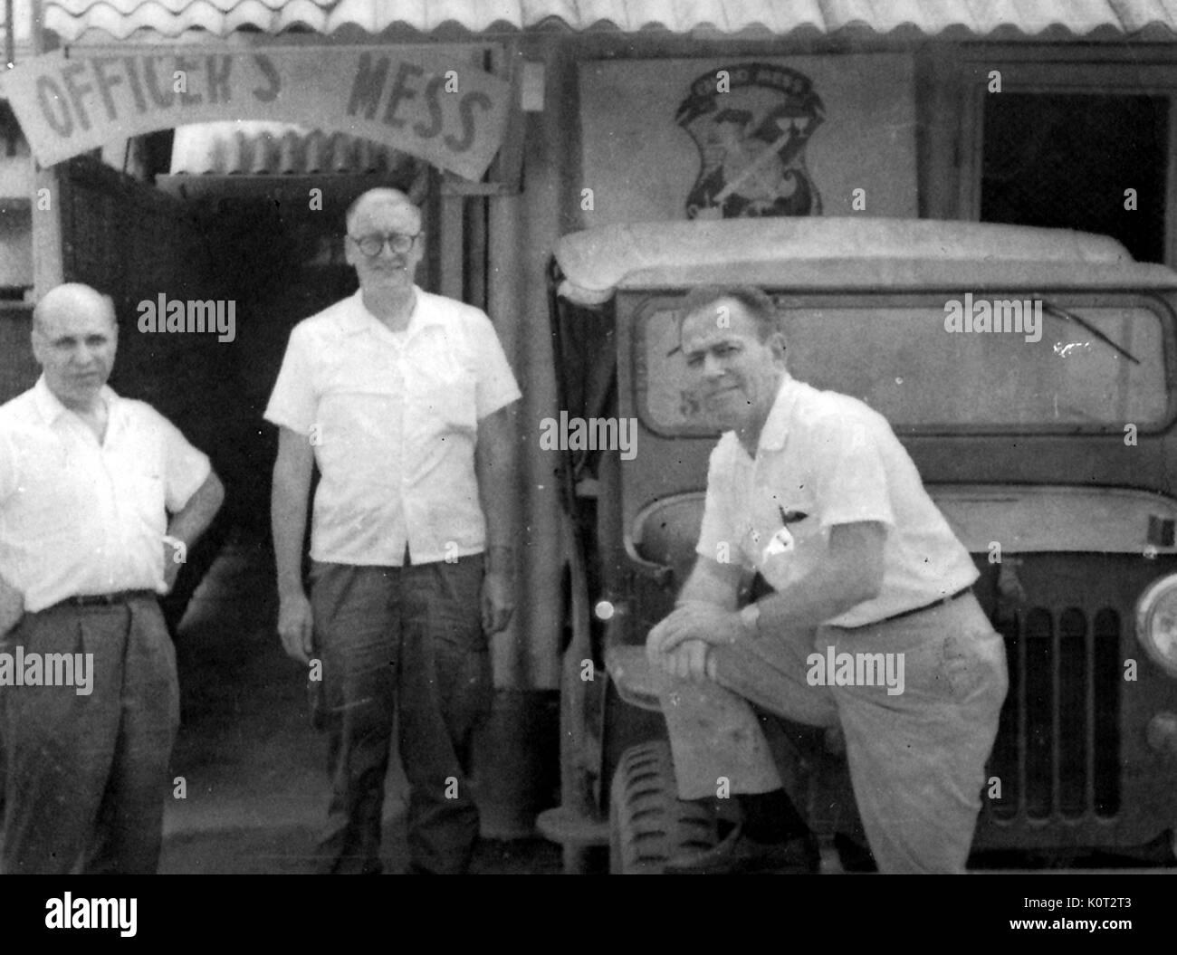 3 United States military officers standing in front of an officers mess hall in Vietnam during the Vietnam War, one officer with his foot up on the tire of a Jeep, 1966. - Stock Image