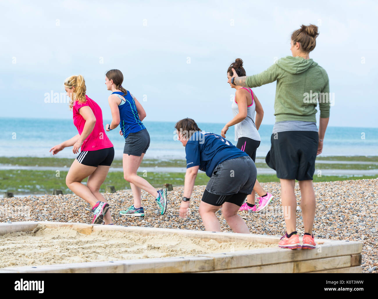Exercise class on a beach. Small group of young women in a fitness class exercising on a beach in the morning in - Stock Image