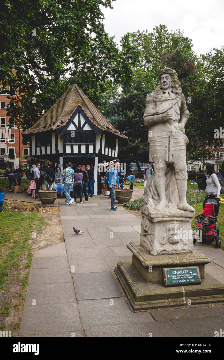Soho Square with the Tudor cottage and the Charles II statue. London 2017. Portrait format. - Stock Image