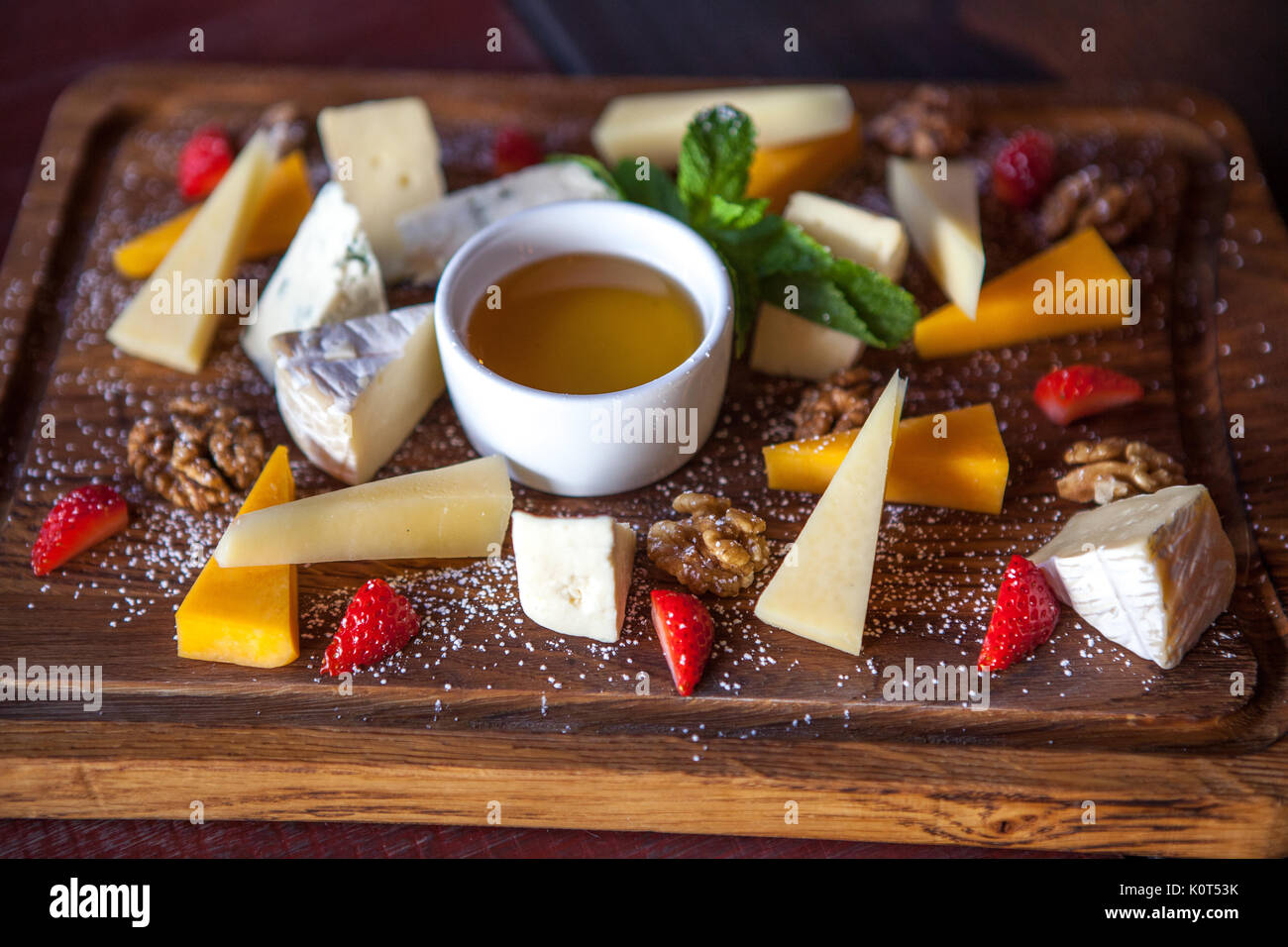 various cheeses with nuts and berries on a wooden Board - Stock Image