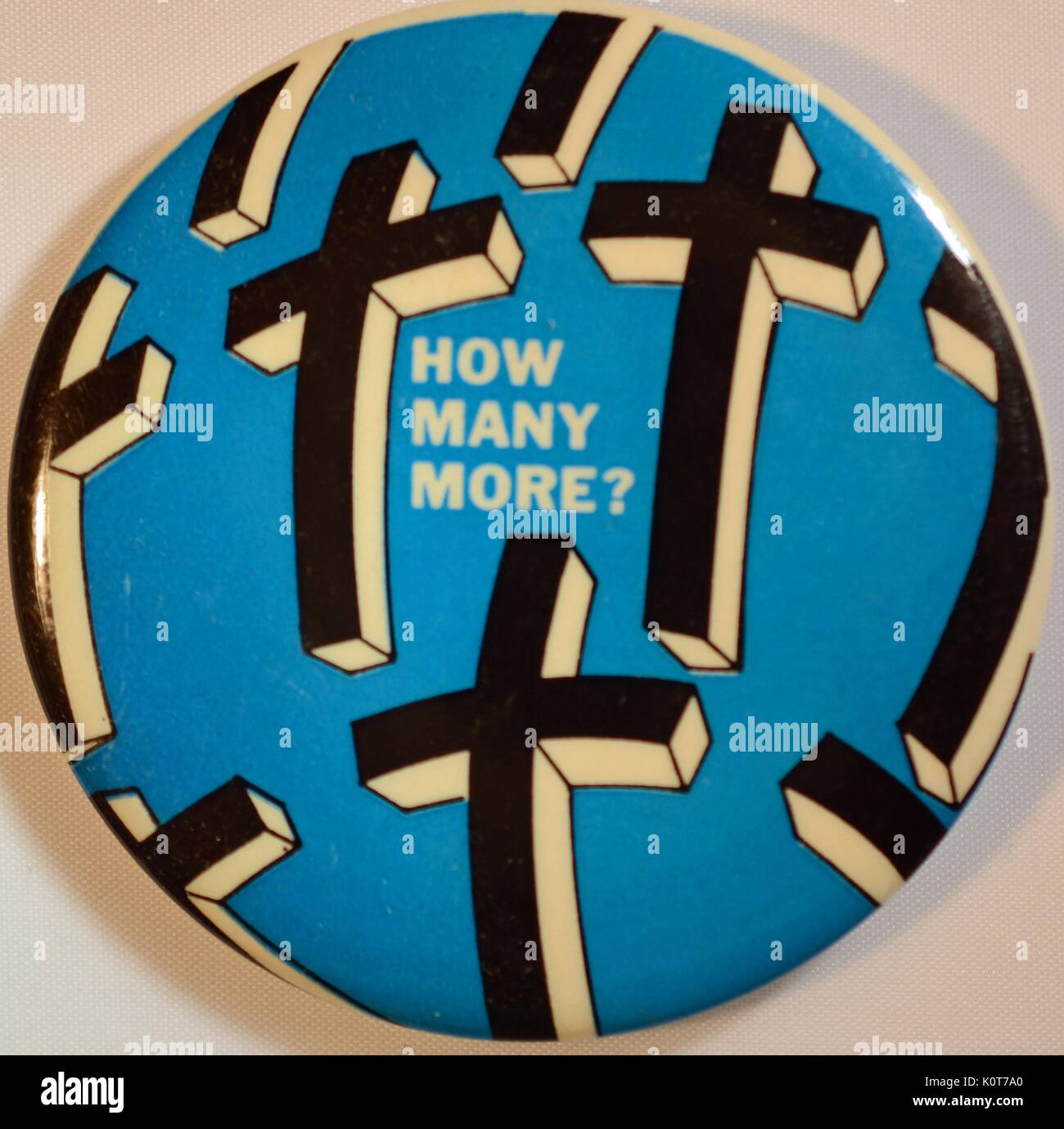 An anti-Vietnam War protest pin that features a blue background and black and white images of crosses, it also features the text 'How many more?', 1970. - Stock Image