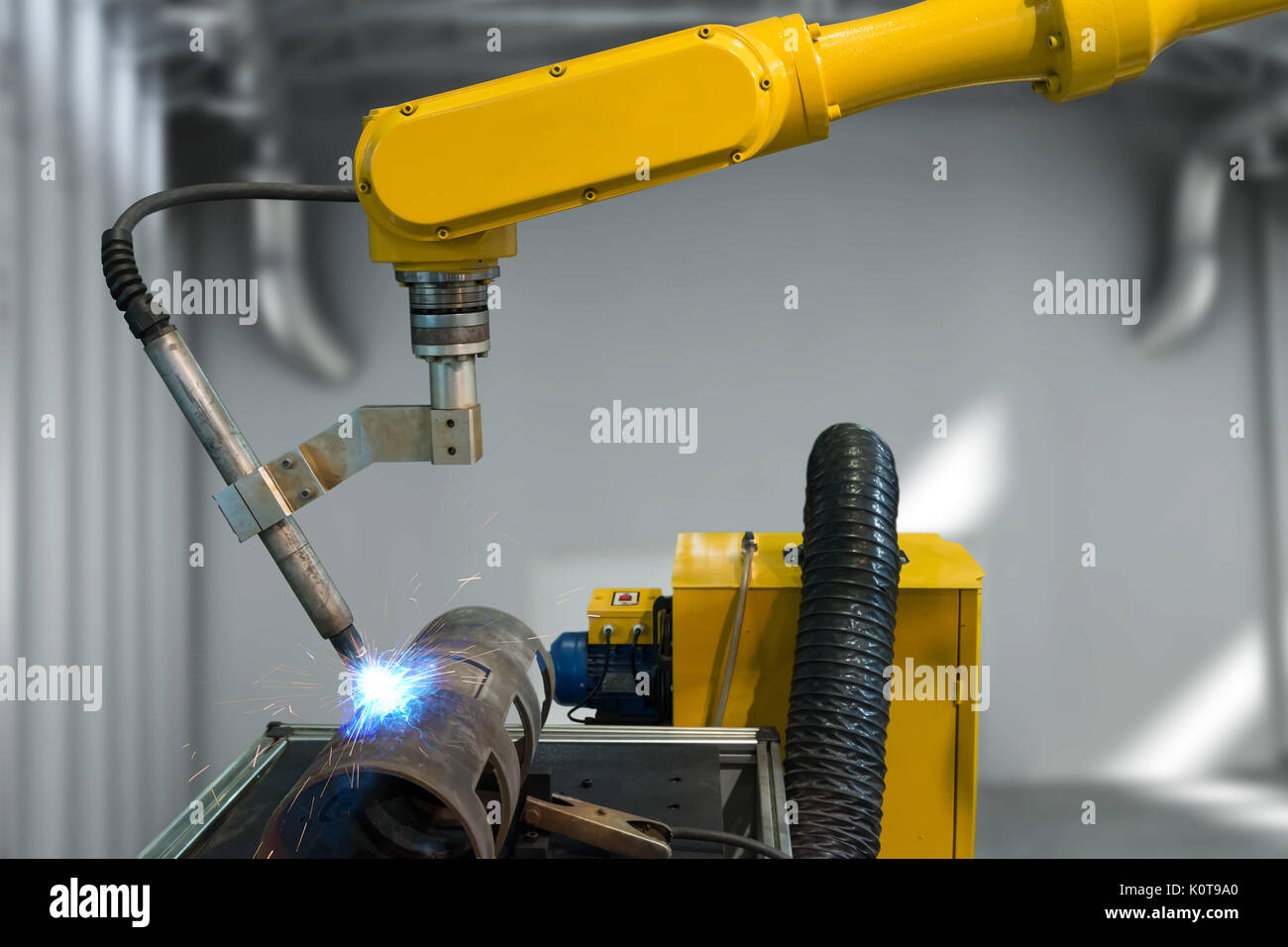 Industry 4.0 technology concept. Automate wireless welding Machine Robot arm in smart factory. - Stock Image
