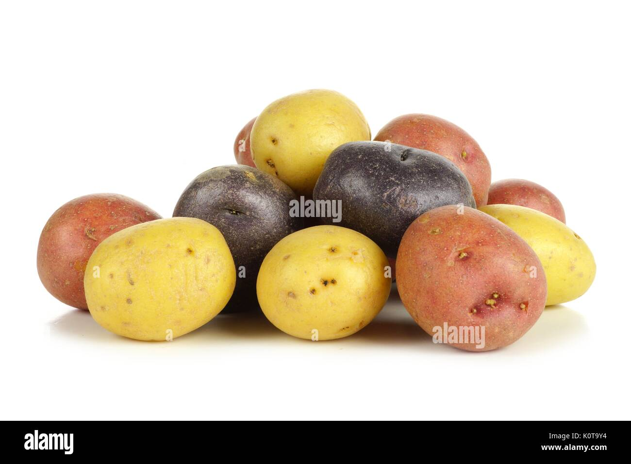 Pile of colorful fresh little potatoes over a white background - Stock Image