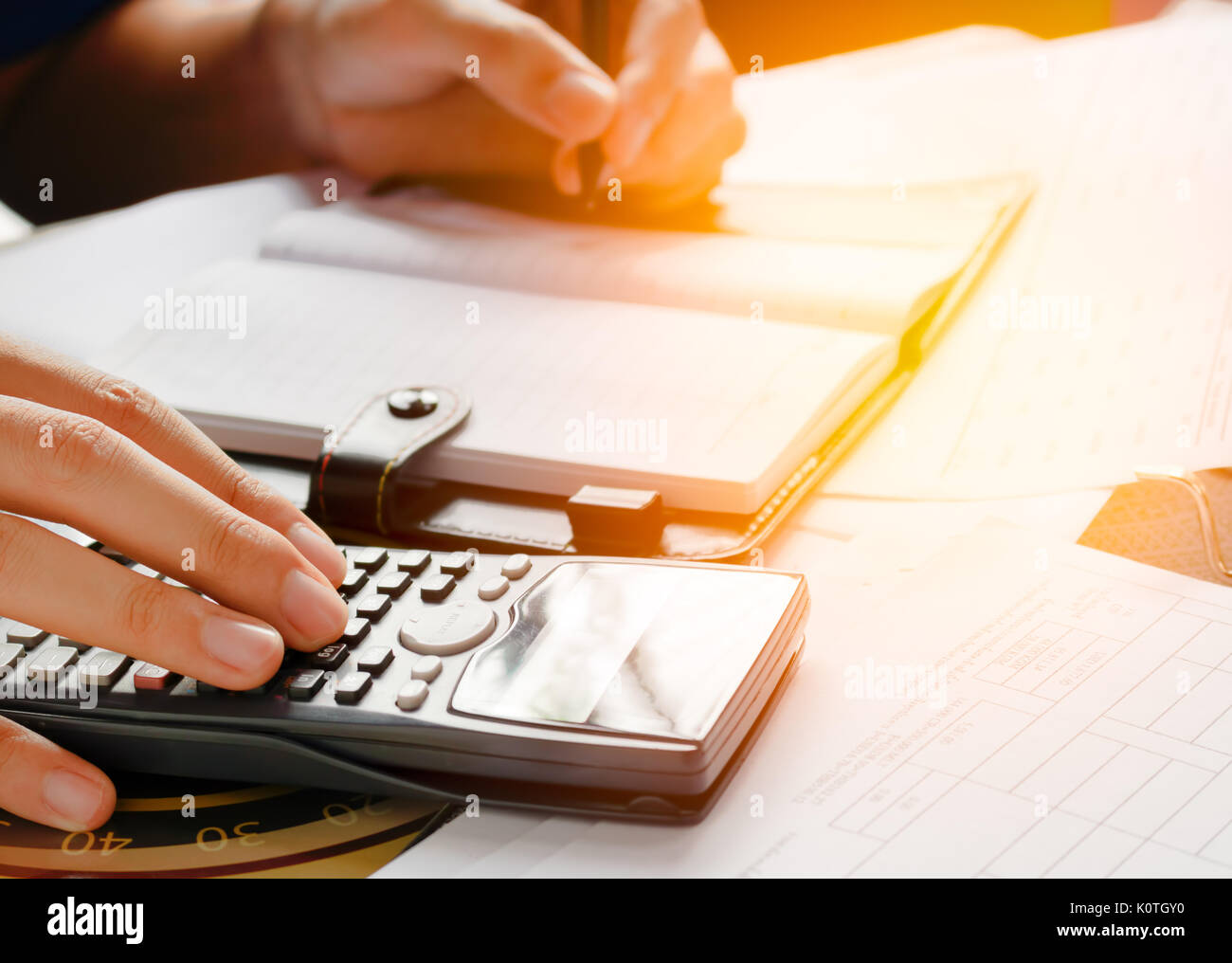 close up, business man or lawyer accountant working on accounts using a calculator and writing on documents, soft focus - Stock Image