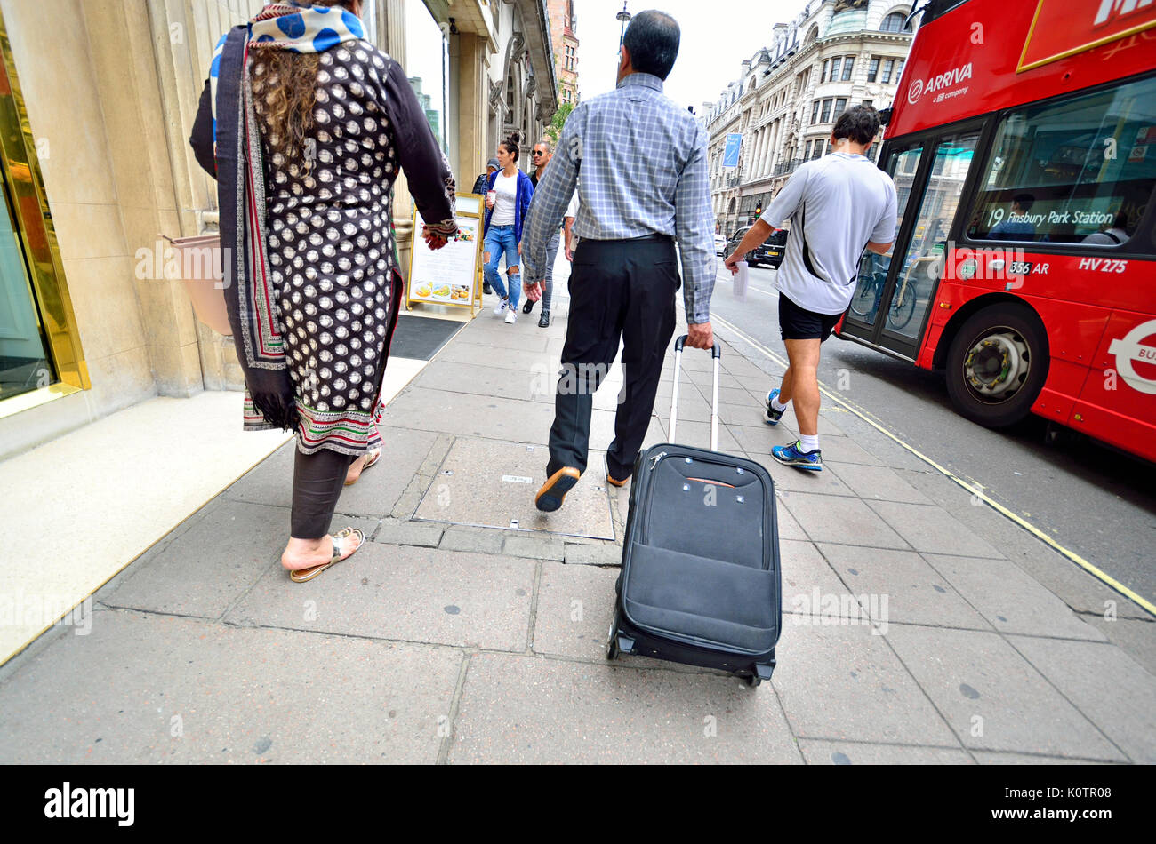 London, England, UK. Man pulling a wheeled suitcase in the street - Stock Image