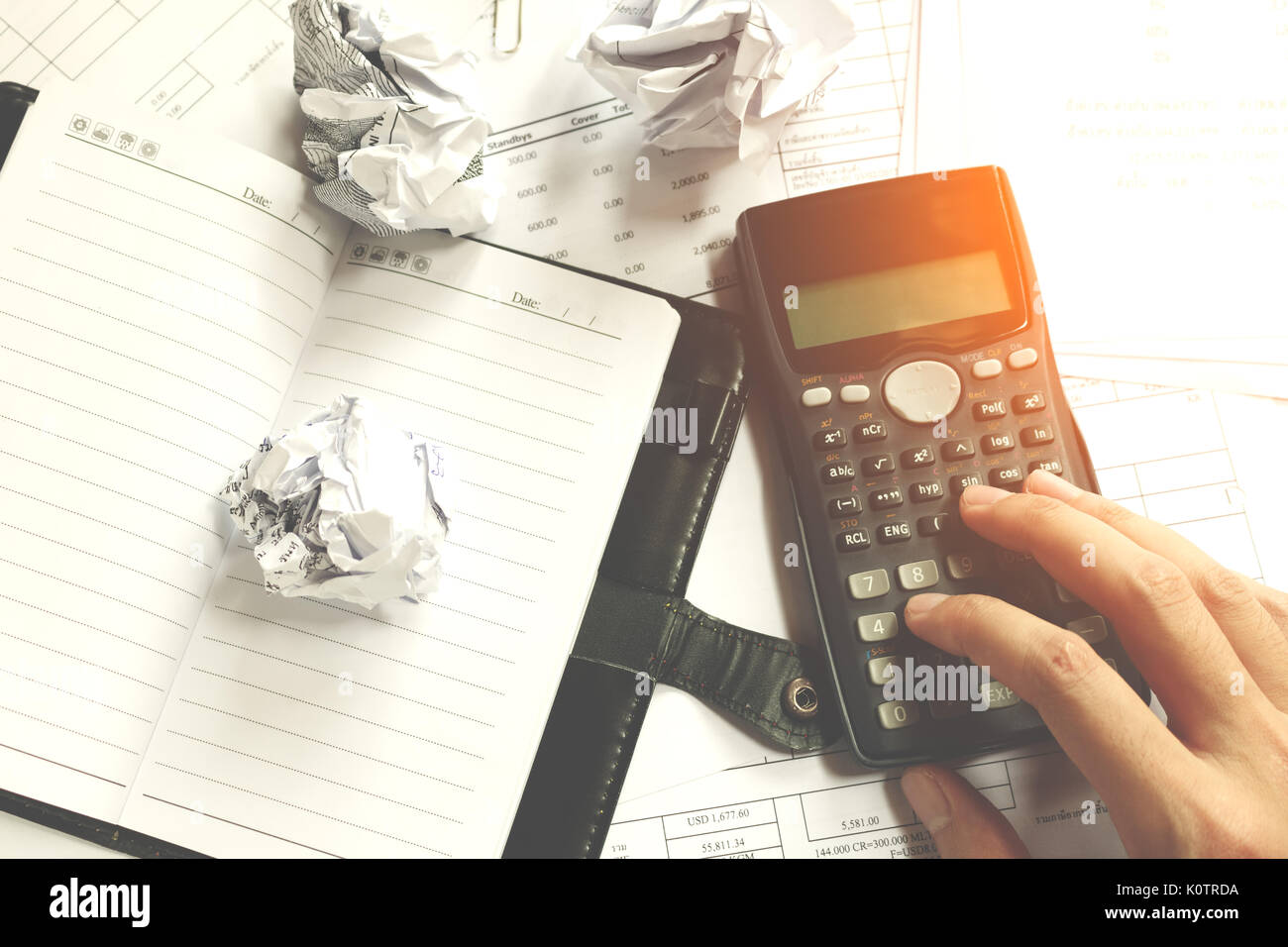Businessman sitting at desk in a little office or home mad at work, ripping documents. Throwing around scraps of paper. Negative human emotions, soft  - Stock Image