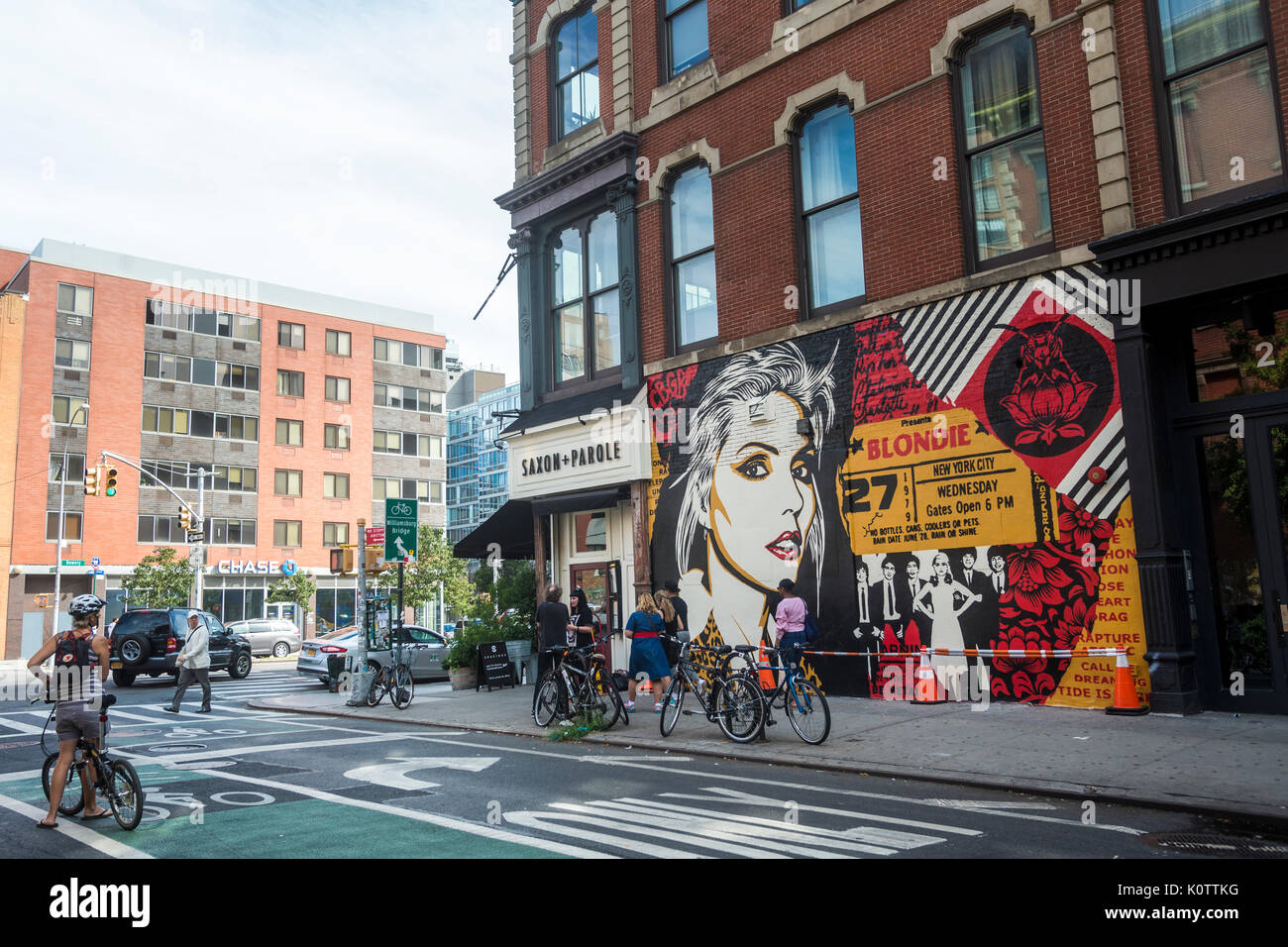 """New York, USA. 23rd Aug, 2017. Passersby stop to admire a newly completed mural, by Shepard Fairey, in the East Villagehe mural features Debbie Harry, lead singer for the rock group Blondie, who got their start in 1979 at CBGB which was located across the street. Fairy's work is also featured in Blondie's latest album """"Polinator"""" which was released in May 2017. Credit: Stacy Walsh Rosenstock/Alamy Live News - Stock Image"""