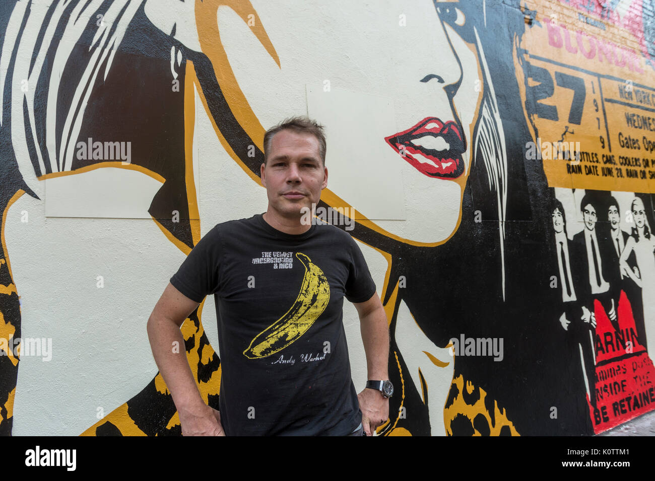 """New York, USA. 23rd Aug, 2017. Shepard Fairey, and his newly completed mural. The mural features Debbie Harry, lead singer for the rock group Blondie, who got their start in 1979 at CBGB which was located across the street. Fairy's work is also featured in Blondie's latest album """"Polinator"""" which was released in May 2017. Credit: Stacy Walsh Rosenstock/Alamy Live News - Stock Image"""