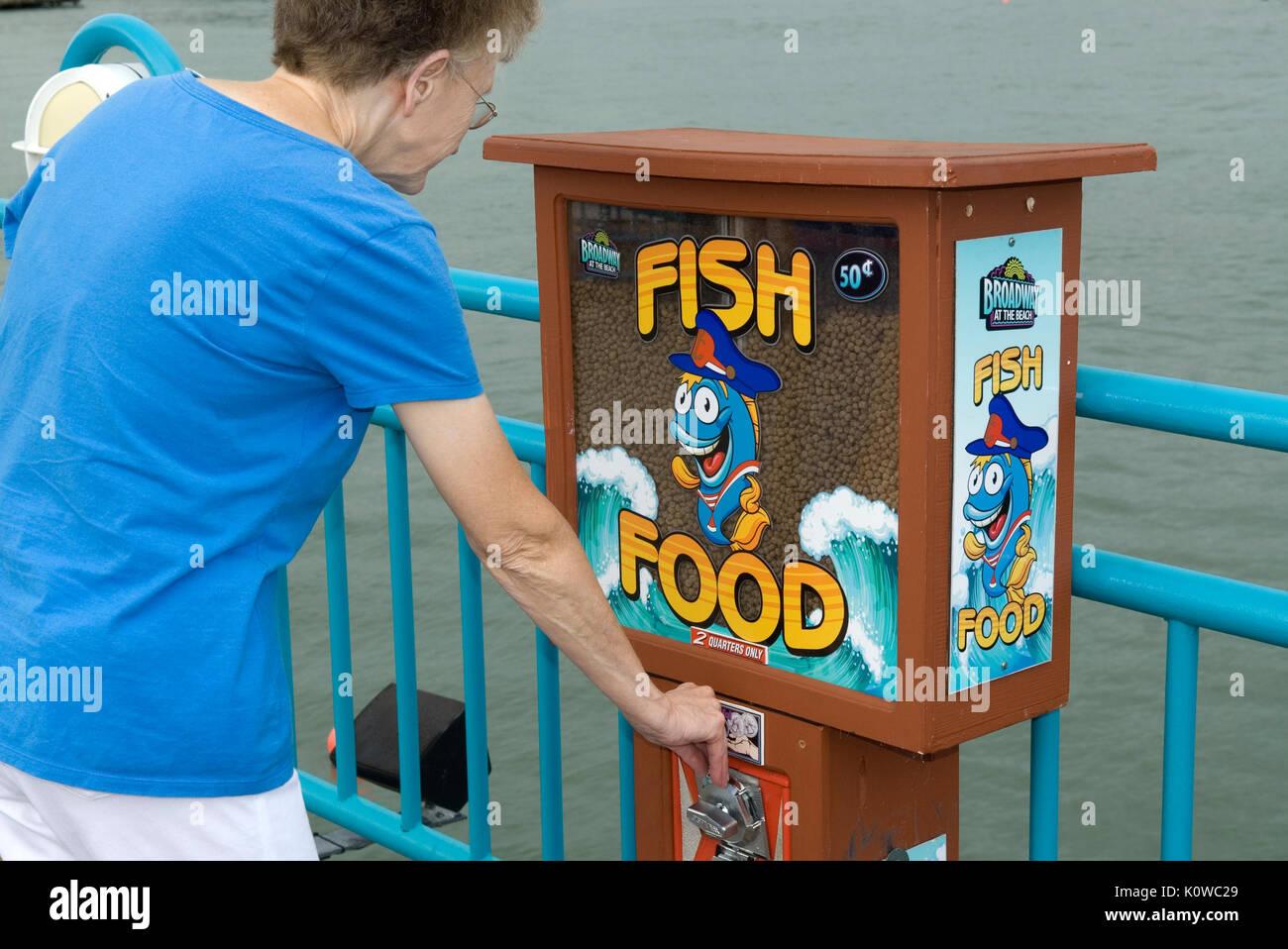 Caucasian Senior Woman Buying Fish Food at Broadway at the Beach, Myrtle Beach South Carolina USA. - Stock Image