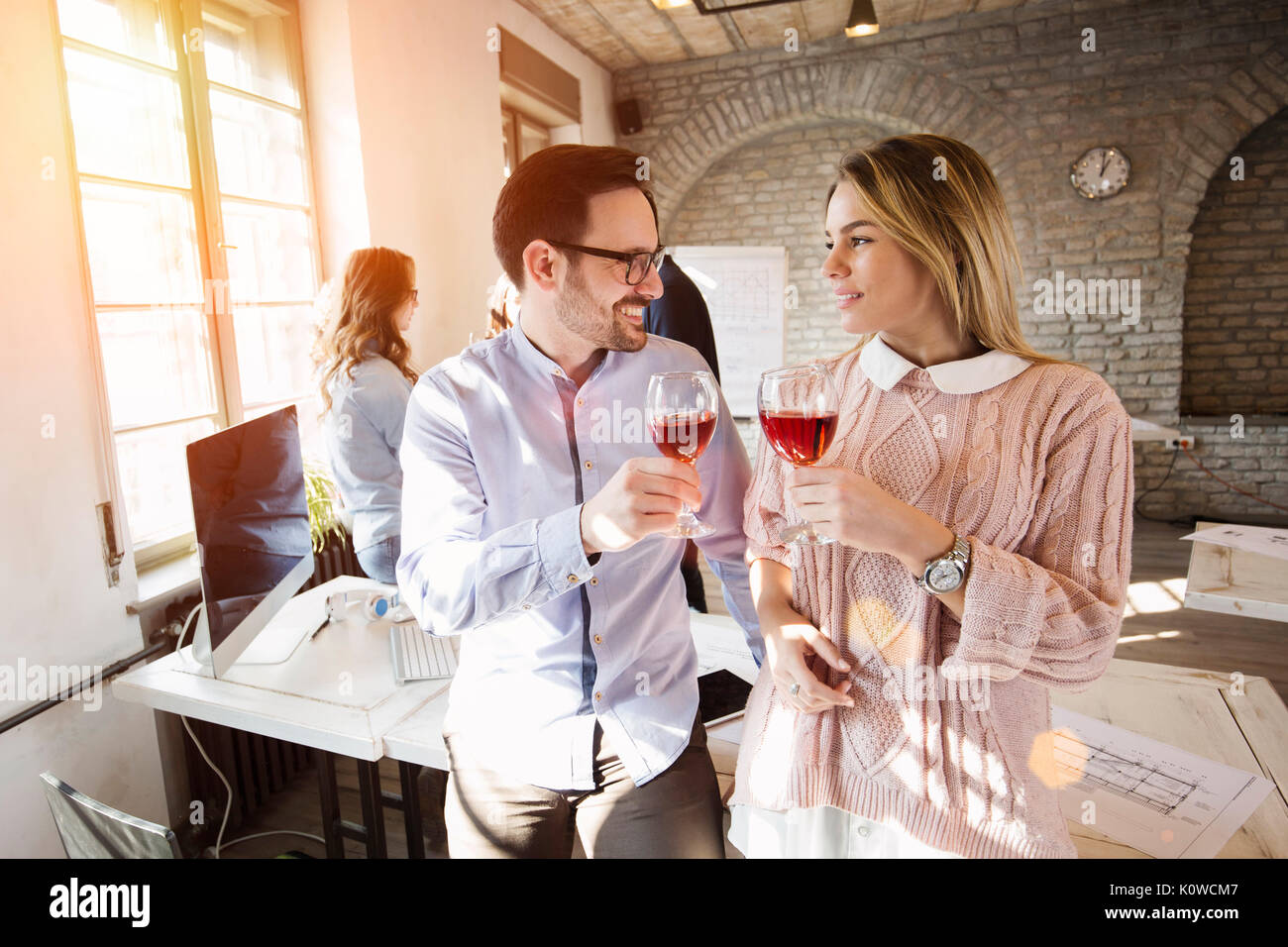 Happy young architects having break and drinking wine - Stock Image