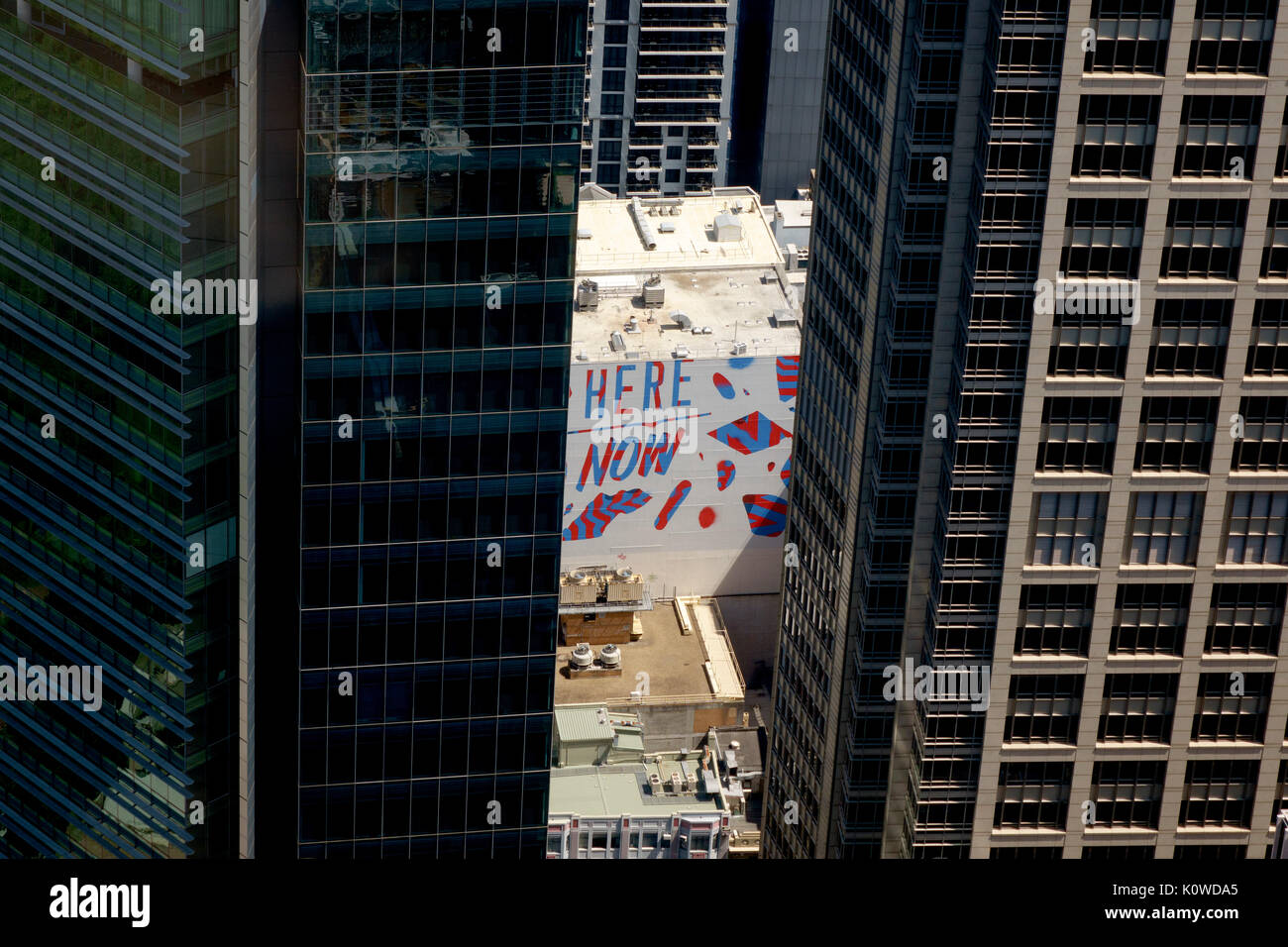 Skyscrapers Framing A Here Now Sign Painted On A Smaller Skyscraper Building Sydney Australia, Aerial View From Sydney Tower Eye - Stock Image