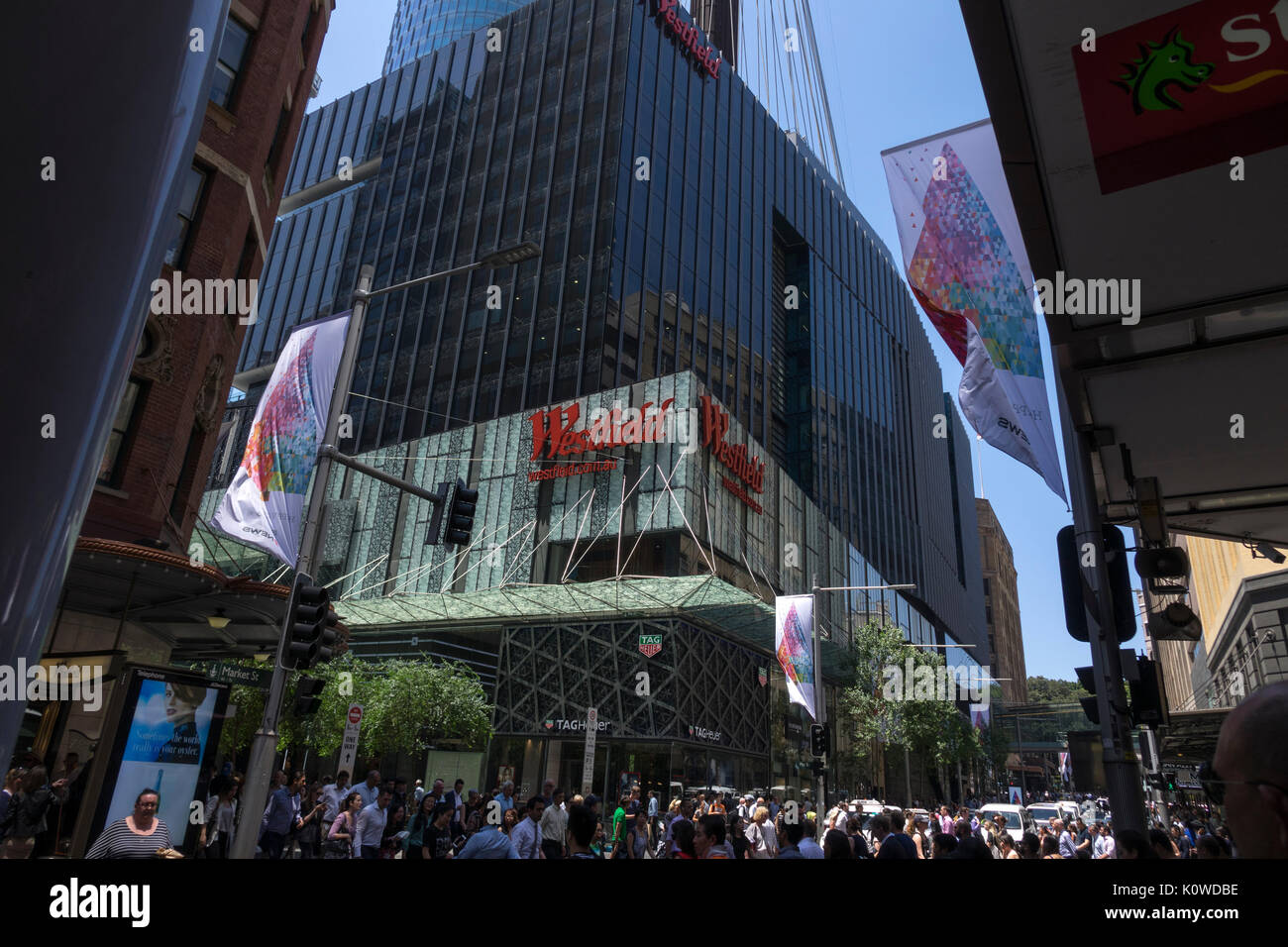 Pedestrians Cross The Street In Front Of Westfield Sydney A Shopping Centre Mall Under The Sydney Tower Eye Australia - Stock Image