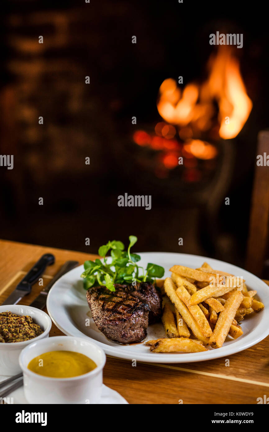 Steak and chips by the fireside - Stock Image