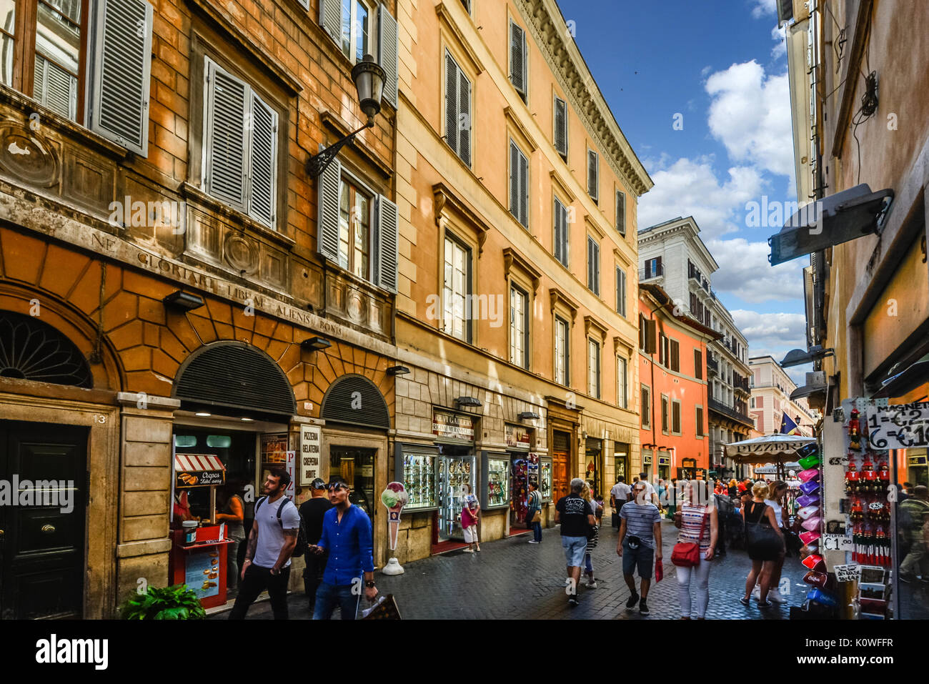 A colorful street in Rome Italy as tourists window shop and enjoy the historic downtown area - Stock Image