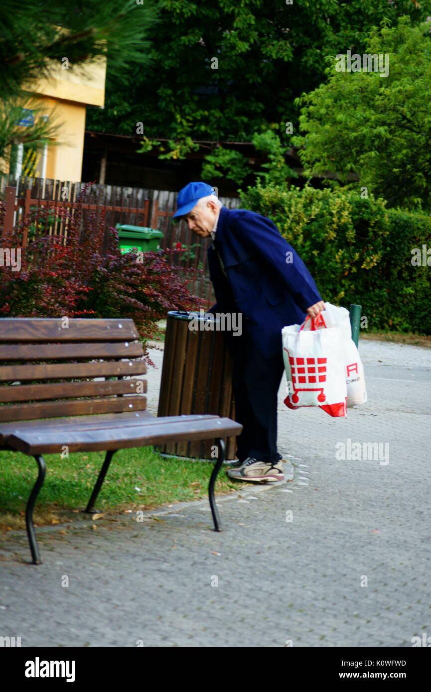 Senior citizen collecting recyclables from the garbage - Stock Image