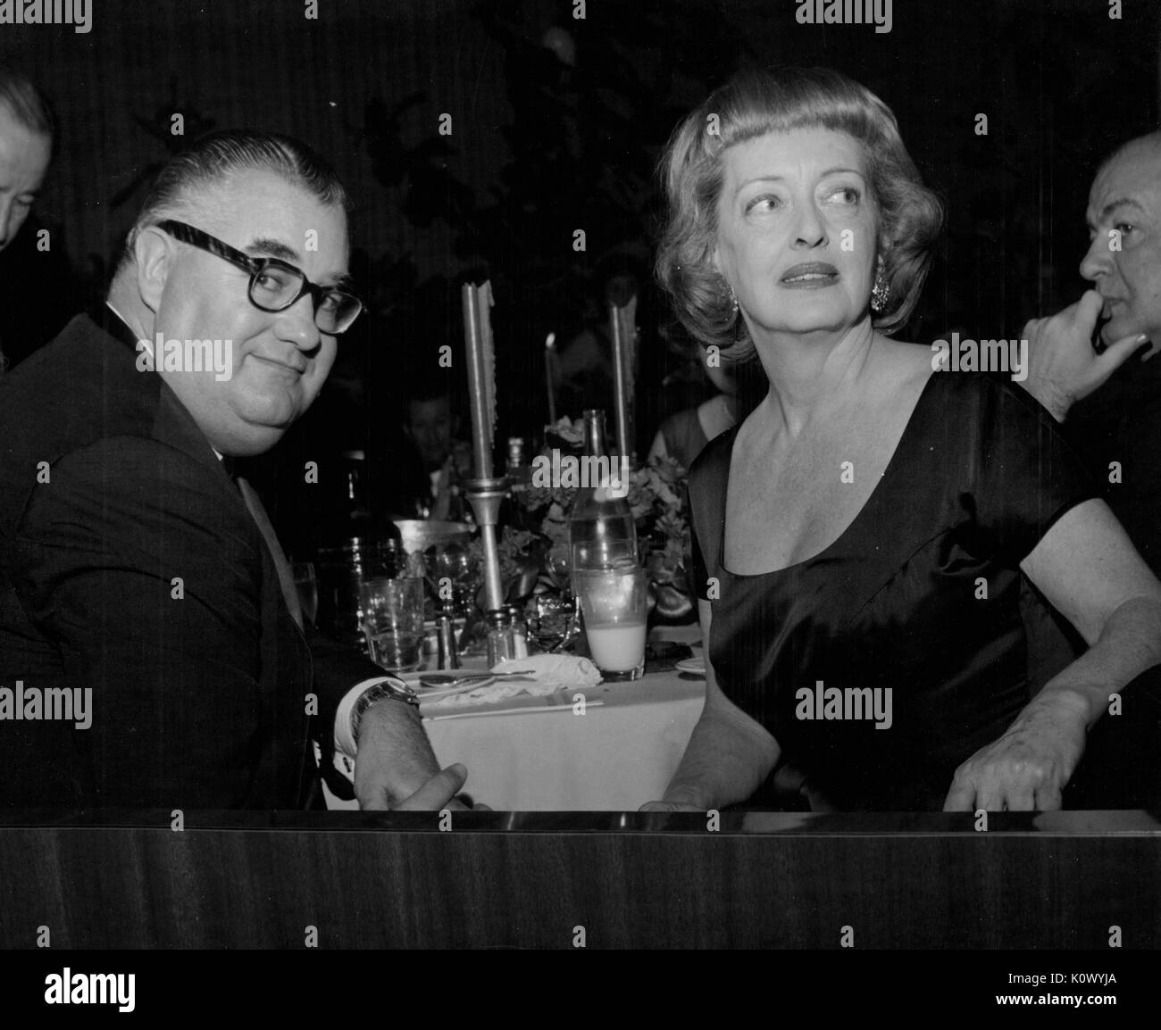 Bette Davis, sitting at a banquet table with an unidentified man, turning around in her chair and looking to her right, in a dark room during a dinner, Hollywood, California, Hollywood, California, 1950. Photo credit Smith Collection/Gado/Getty Images. - Stock Image