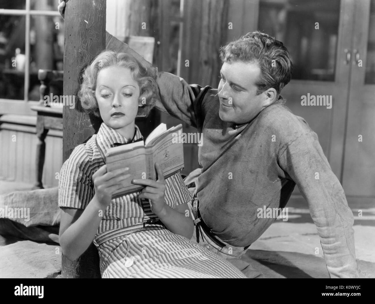 Bette Davis reclining on the floor and reading a book to a man, in a movie still, 1949. Photo credit Smith Collection/Gado/Getty Stock Photo
